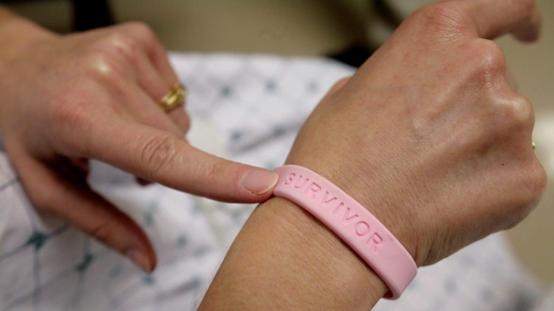 A cancer patient shows off her breast cancer survivor bracelet REUTERS/Jim Bourg
