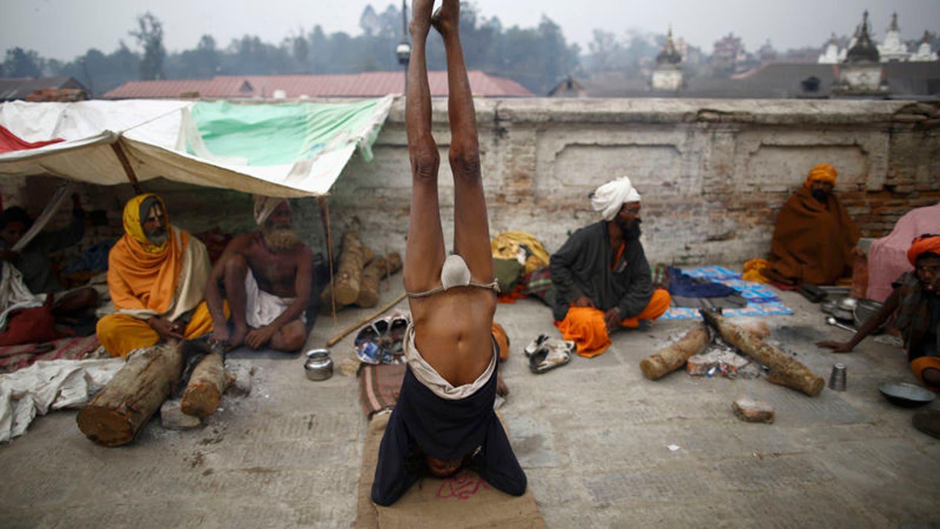 A Hindu holy man, or sadhu, performs yoga at the premises of Pashupatinath Temple in Kathmandu February 26, 2014. REUTERS/Navesh Chitrakar