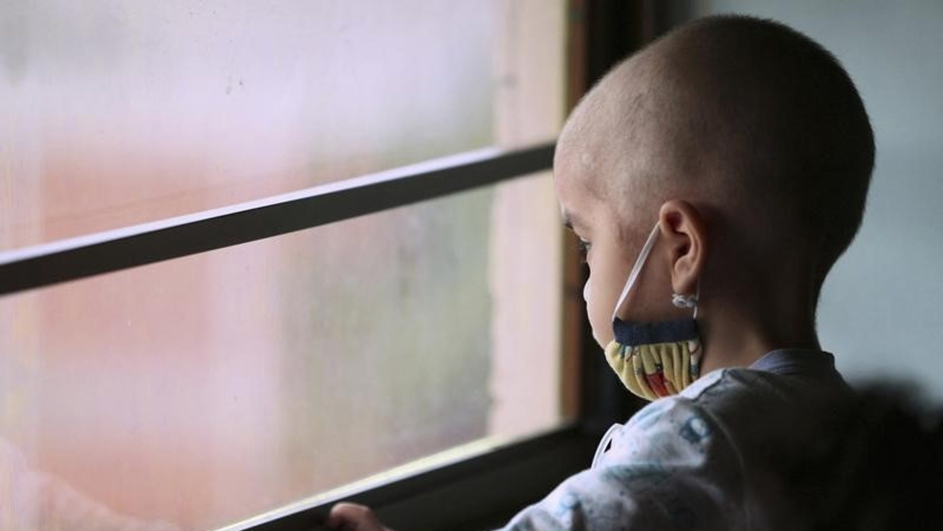 Manuel Andres Sequera, 2, looks out the window while receiving chemotherapy treatment at a paediatric hospital in Maracaibo, Venezuela. November 29, 2011. REUTERS/Isaac Urrutia