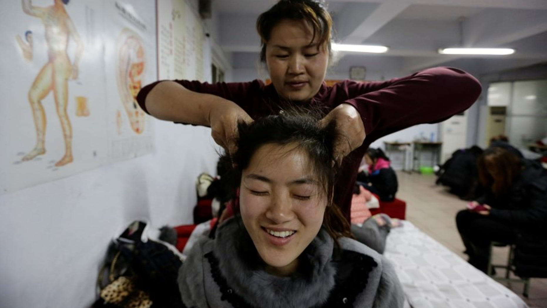 A student presses the acupuncture points on the head of a fellow student as they practise massage on each other during a training course at Huaxia Liangtse Massage Training Center in Zhengzhou, Henan province, February 17, 2014.  REUTERS/Jason Lee