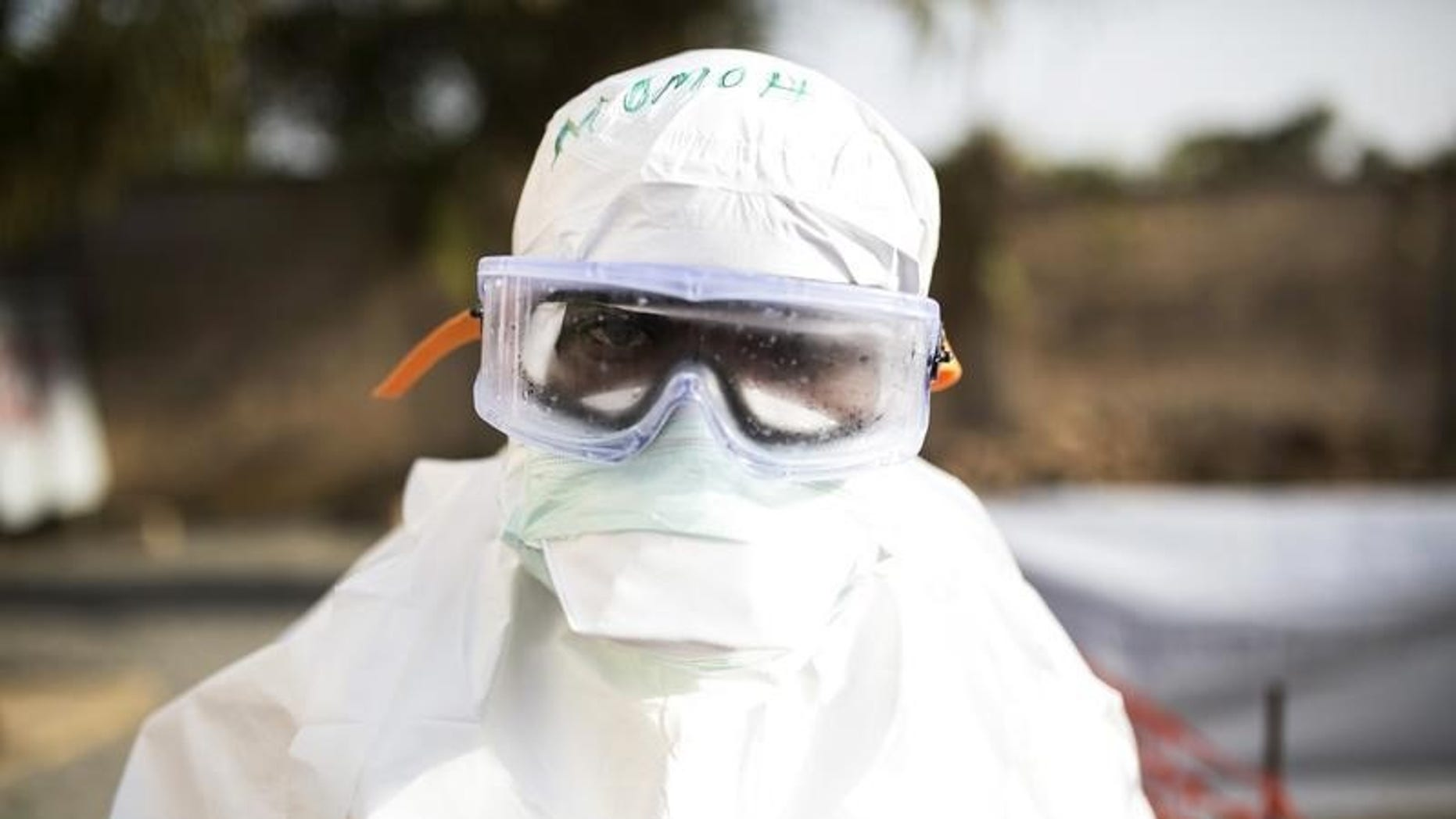 A health worker wearing protective gear stands outside a quarantine zone in a Red Cross facility in the town of Koidu, Kono district in Eastern Sierra Leone December 18, 2014. REUTERS/Baz Ratner