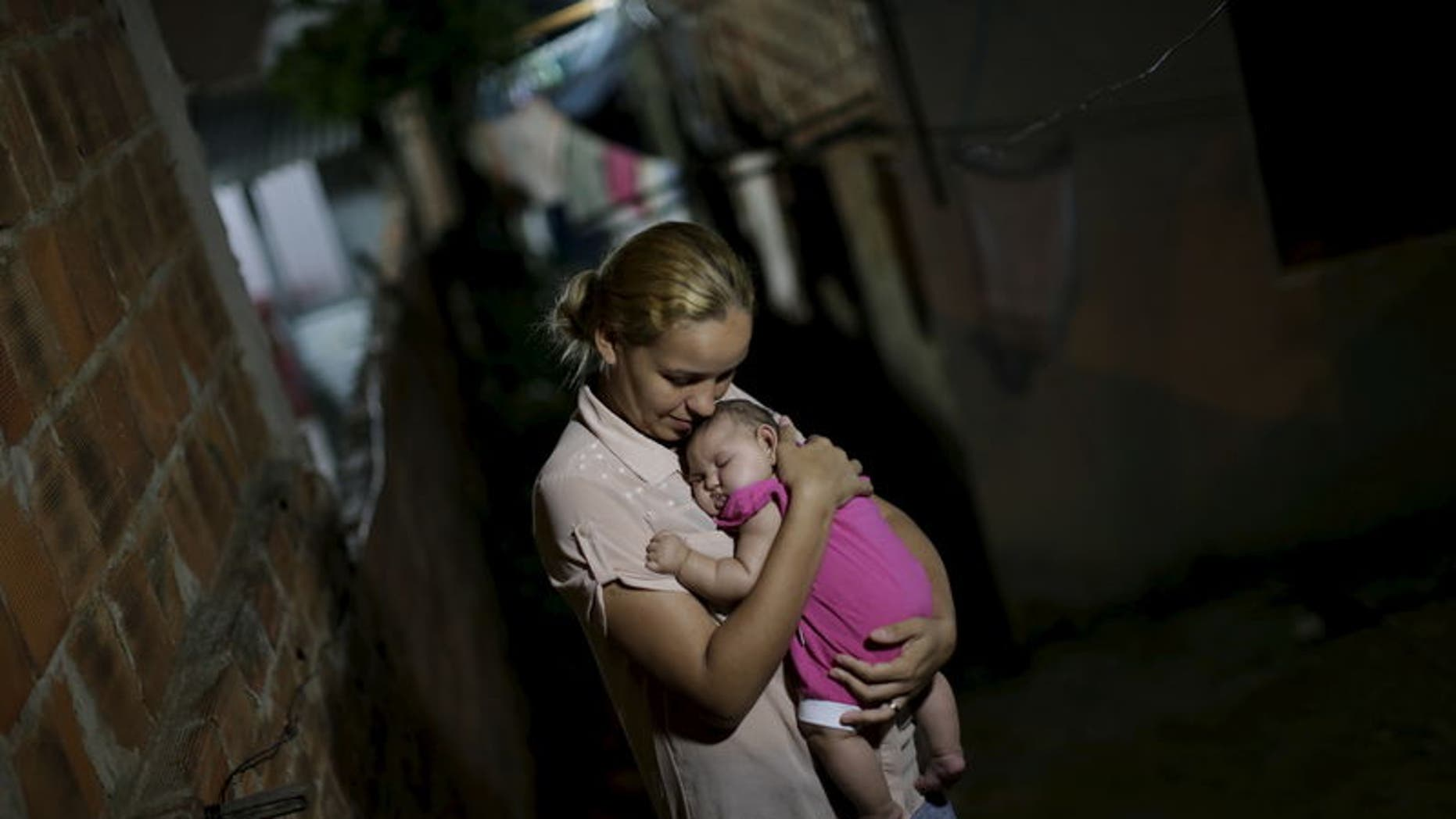 Gleyce Kelly embraces her daughter Maria Geovana, who has microcephaly, in Recife, Brazil, January 25, 2016. REUTERS/Ueslei Marcelino