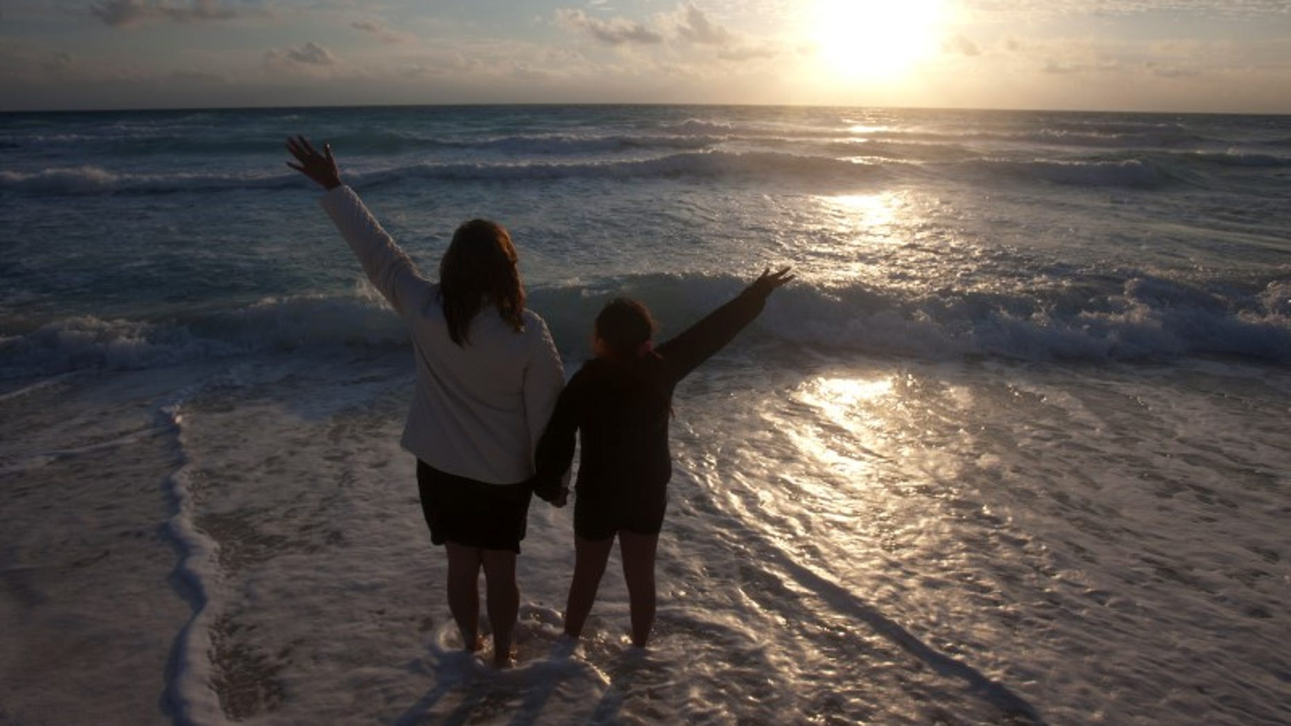 A mother and her daughter raise their hands on a beach at dawn on New Year's Day in Cancun