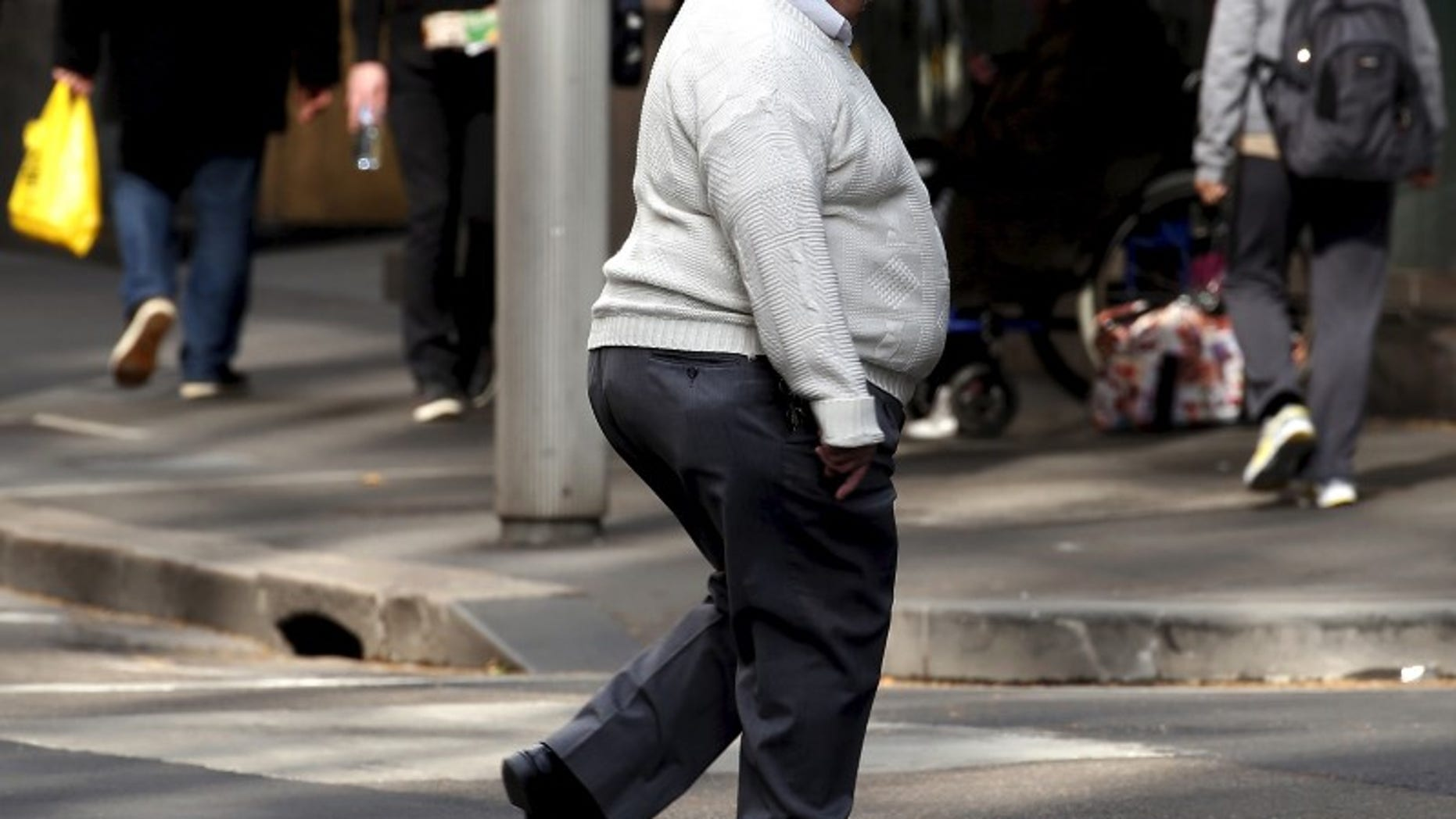 A man crosses a main road as pedestrians carrying food walk along the footpath in central Sydney, Australia