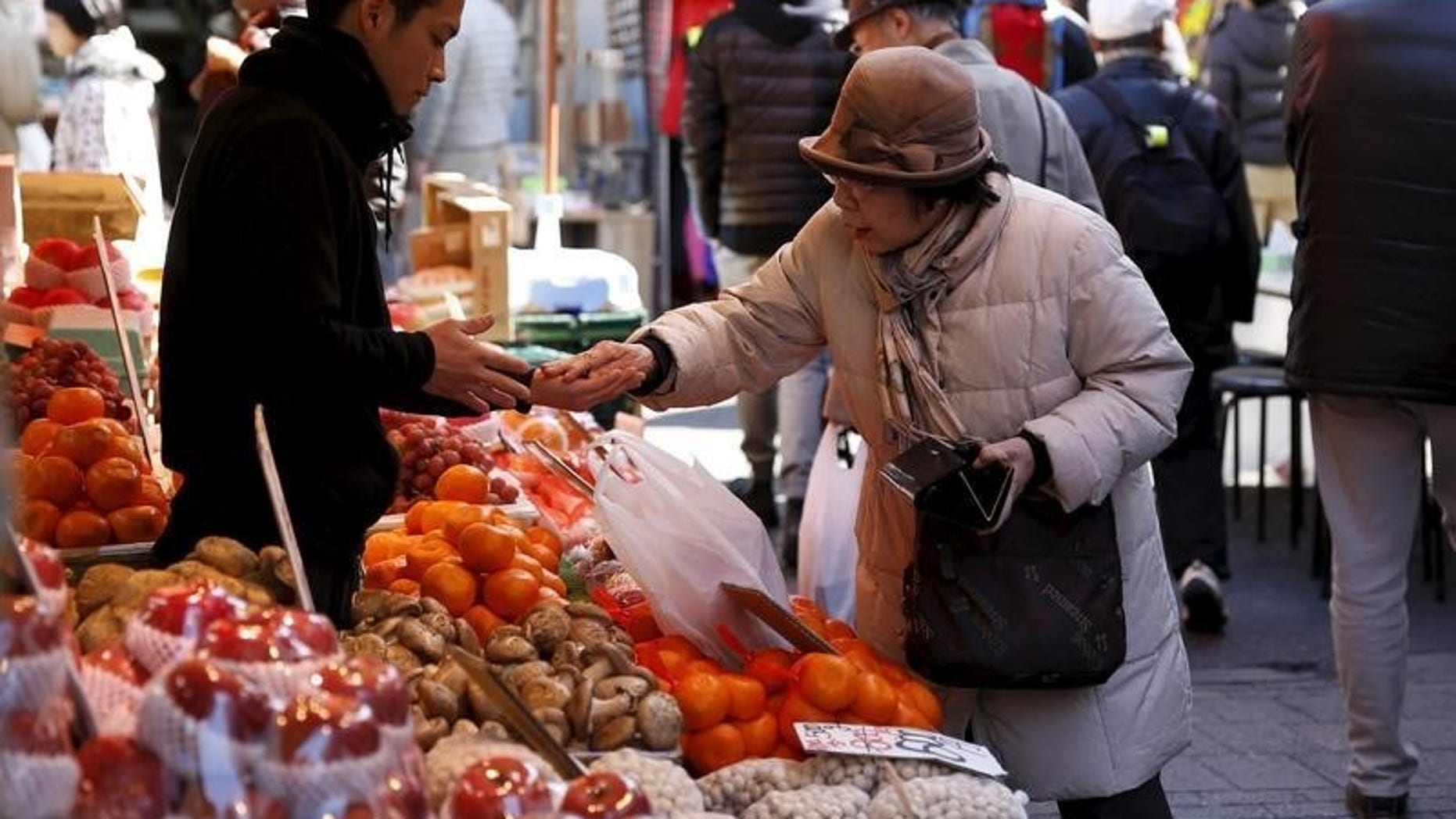 A woman pays money as she buys fruits outside a vegetable store at Ameyoko shopping district in Tokyo