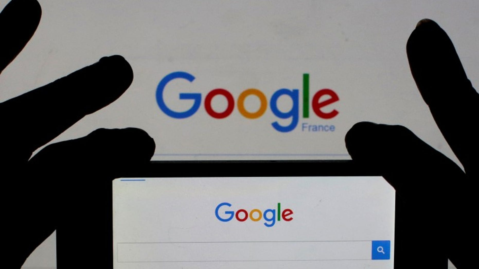 A woman holds her smart phone which displays the Google home page, in this picture illustration