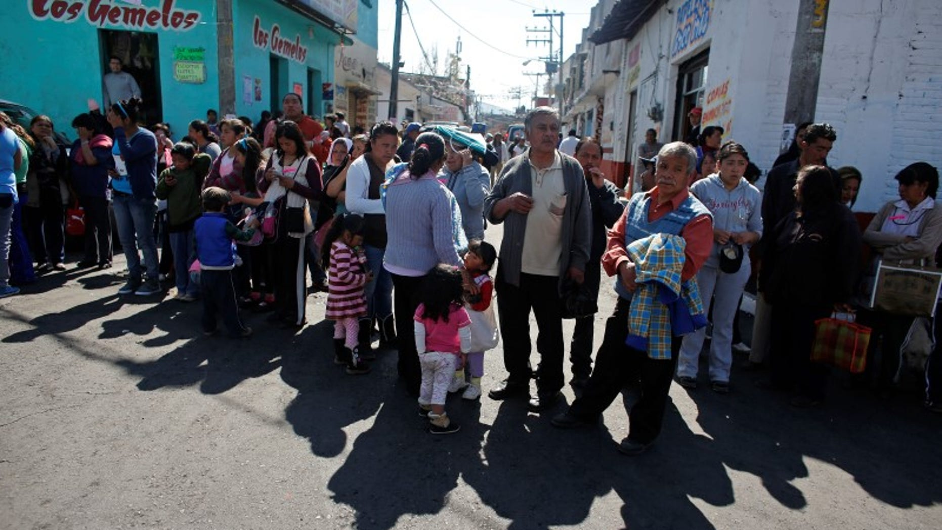 Residents wait in line to receive bedspreads handed out by local authorities at the main plaza of San Lorenzo Acopilco