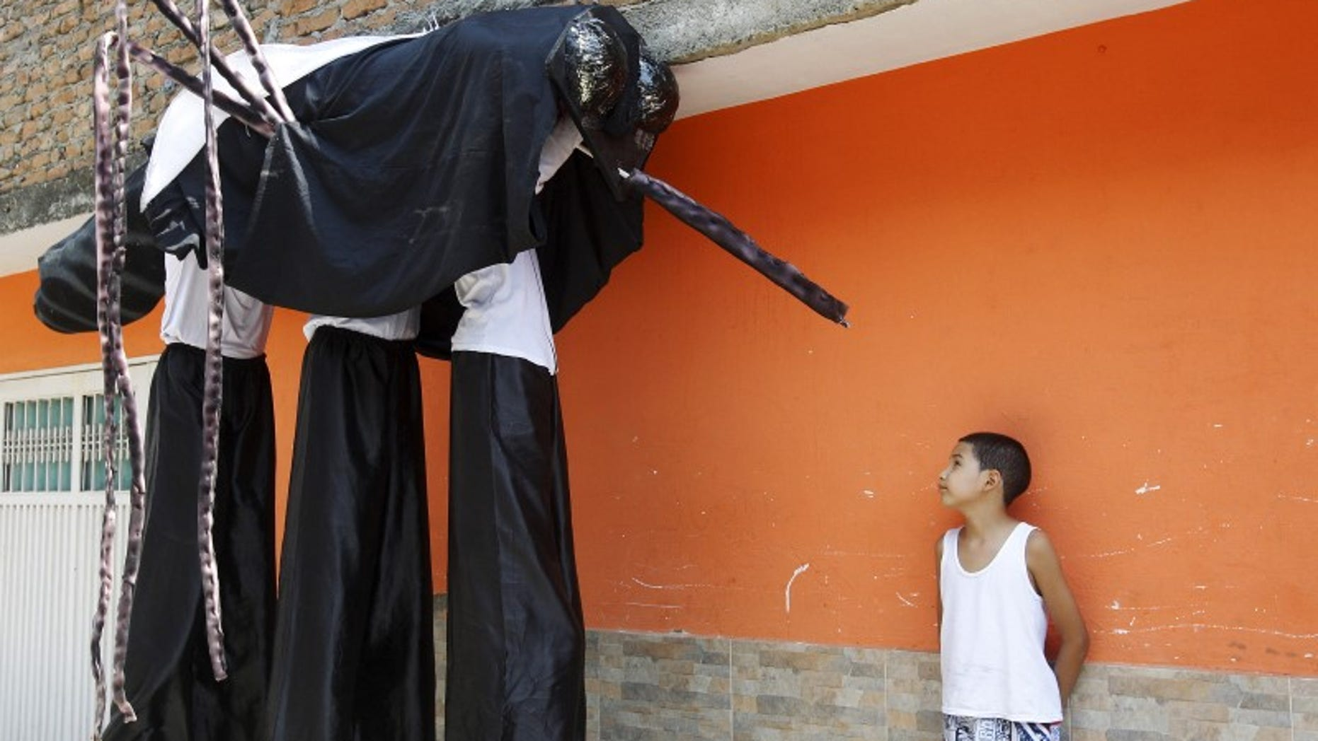 A child looks at men dressed as a mosquito during a health campaign in Cali