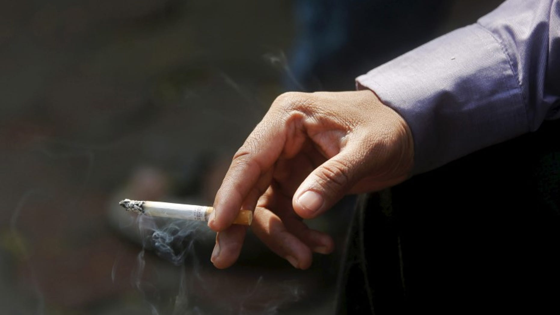 A man smokes a cigarette along a road in Mumbai, India