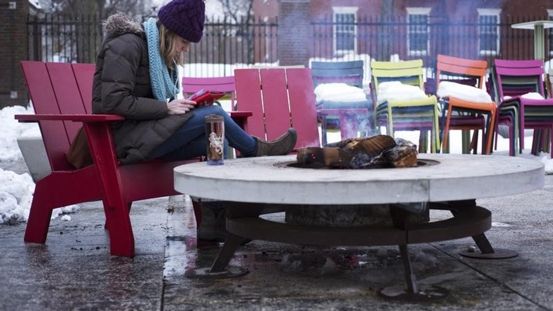 A woman reads a tablet beside a fire pit on cold winter evening outside the Science Center at Harvard University in Cambridge