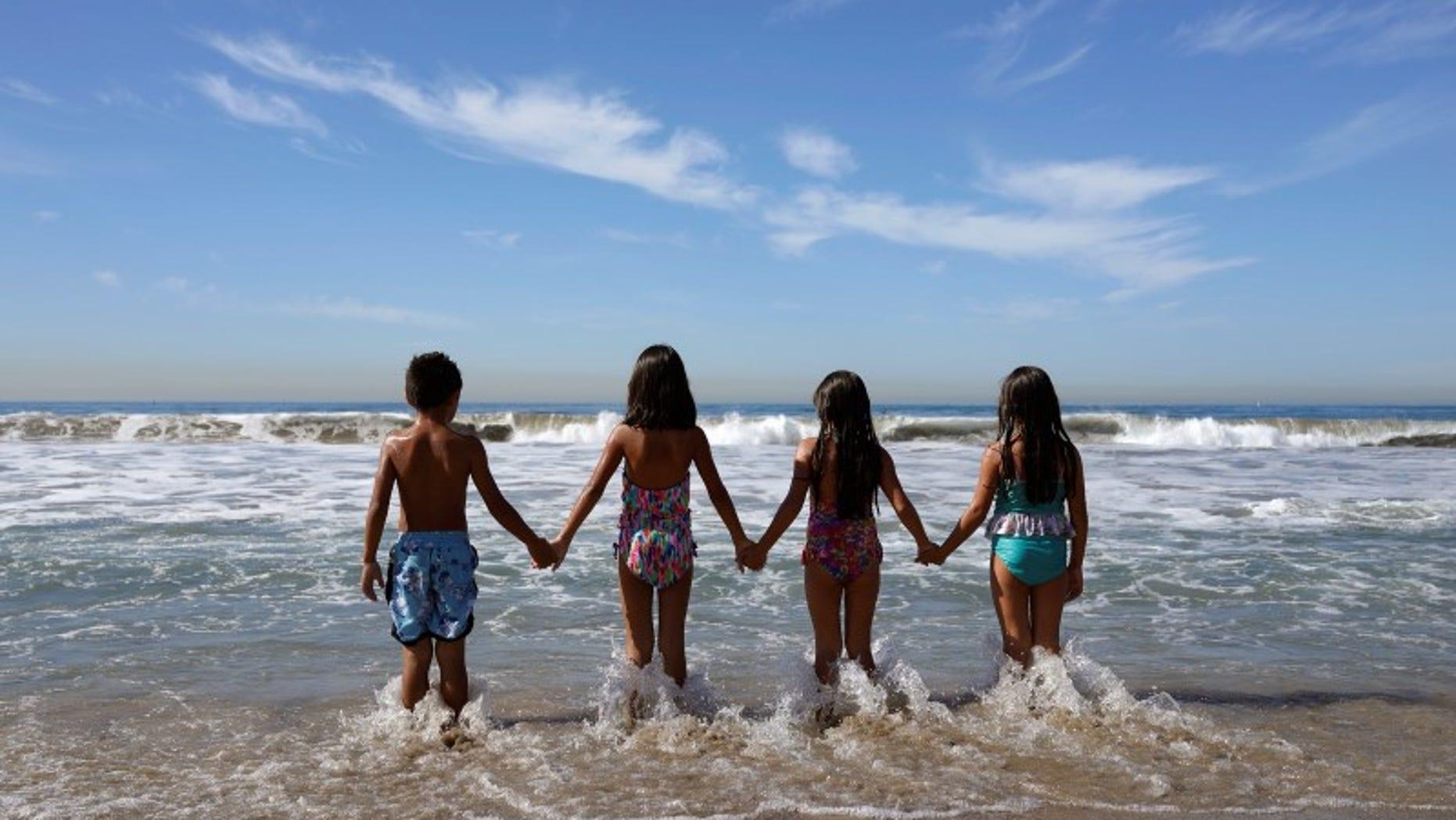Children walk into the Pacific Ocean in Santa Monica
