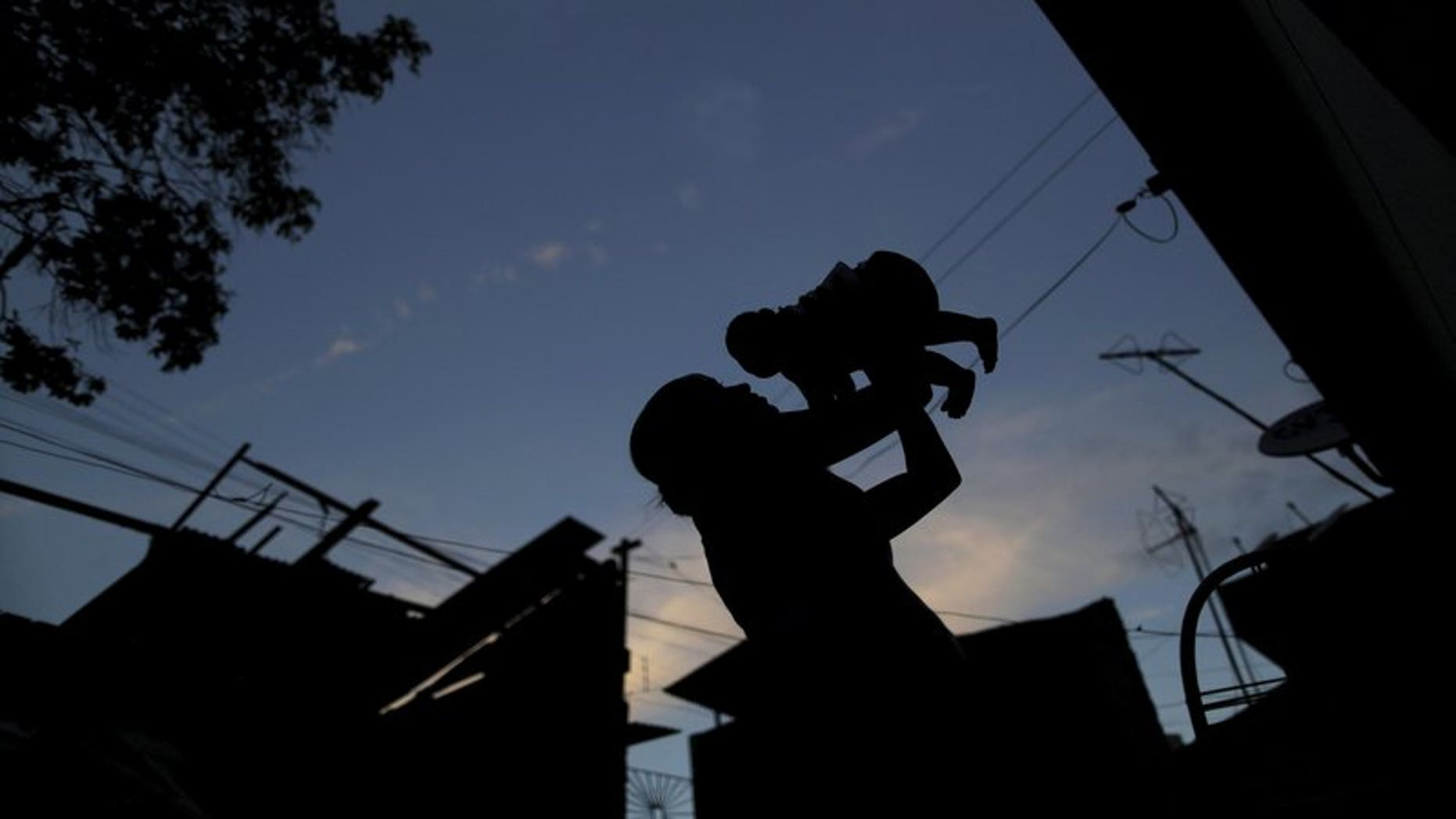 Gleyse Kelly da Silva holds her daughter Maria Giovanna, who has microcephaly, near their house in Recife