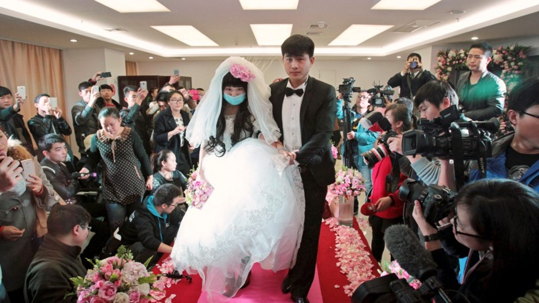 Fan walks on the red carpet with her groom during their wedding at a hospital in Zhengzhou