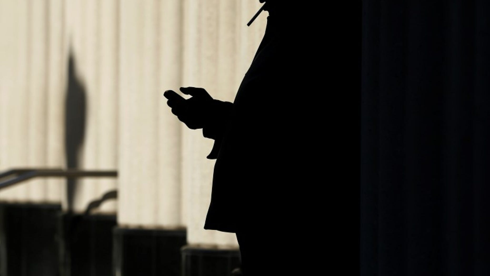 A man sends text messages on his mobile phone as he smokes a cigarette outside the court building in San Diego