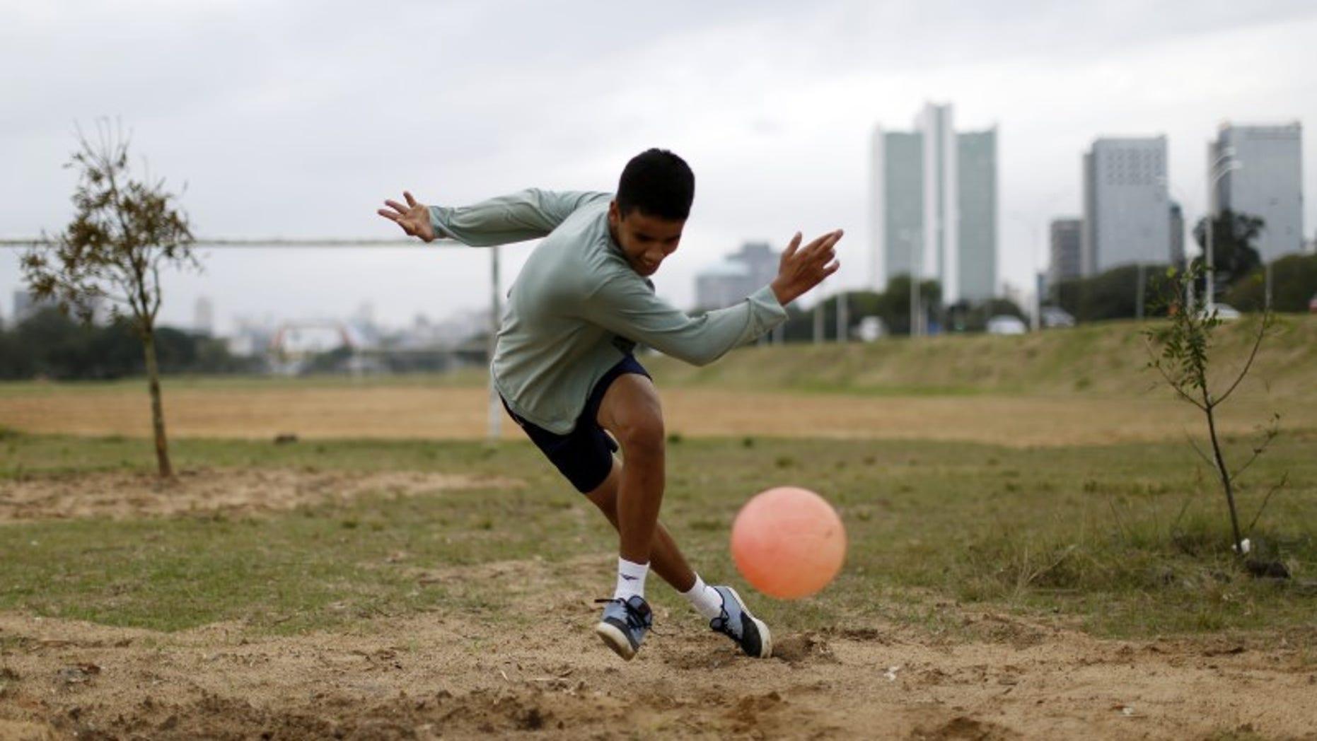 A boy plays soccer in a park in Porto Alegre