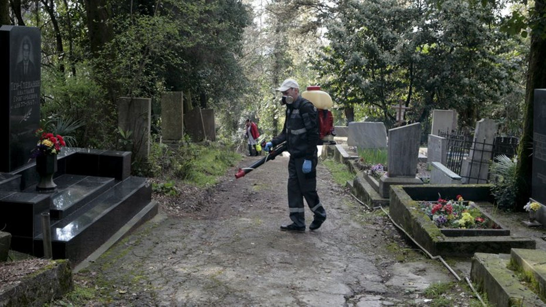 Workers fumigate against mosquito breeding as part of preventive measures against the Zika virus and other mosquito-borne diseases at the cemetery in Sochi