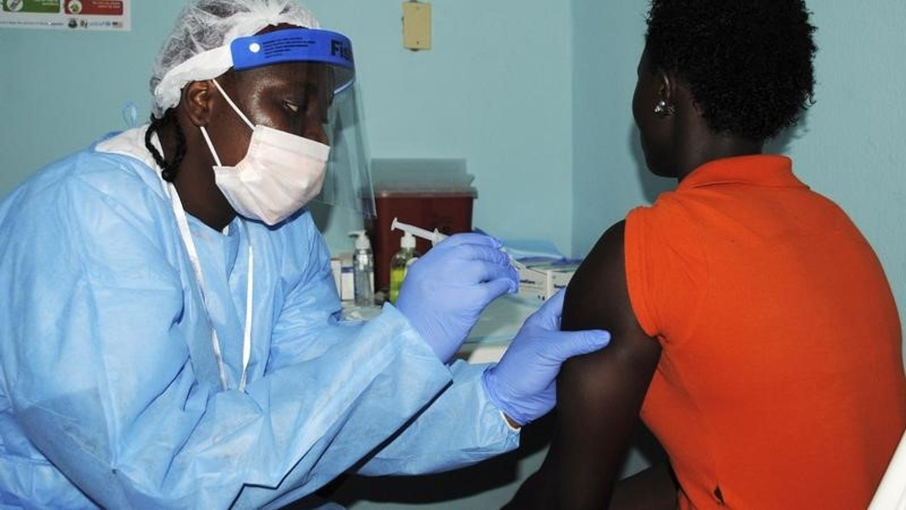 Health worker injects a woman with an Ebola vaccine during a trial in Monrovia