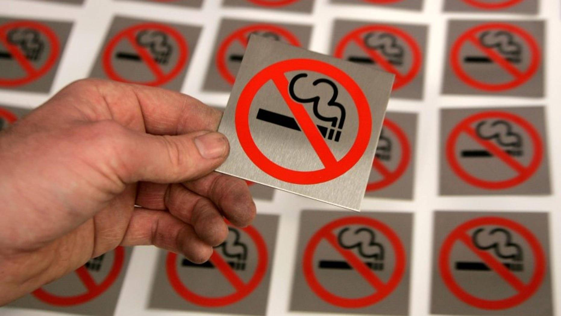 A printer lays a no smoking sign alongside others at First Safety Signs in Bishops Stortford eastern England