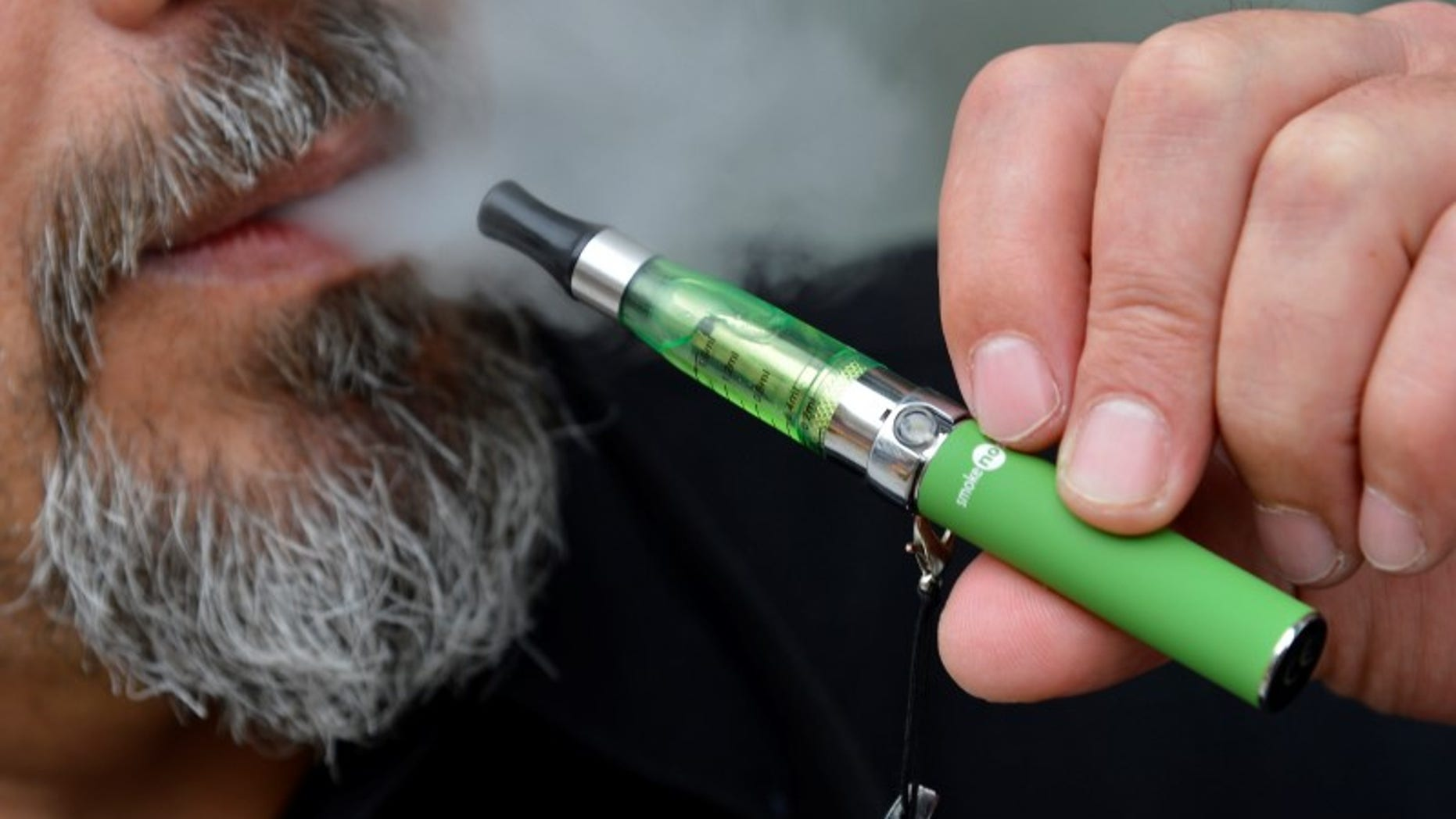 Gabor Kovacs of 'smoke no smoke' puffs on an e-cigarette that his shop sells at Camden in London