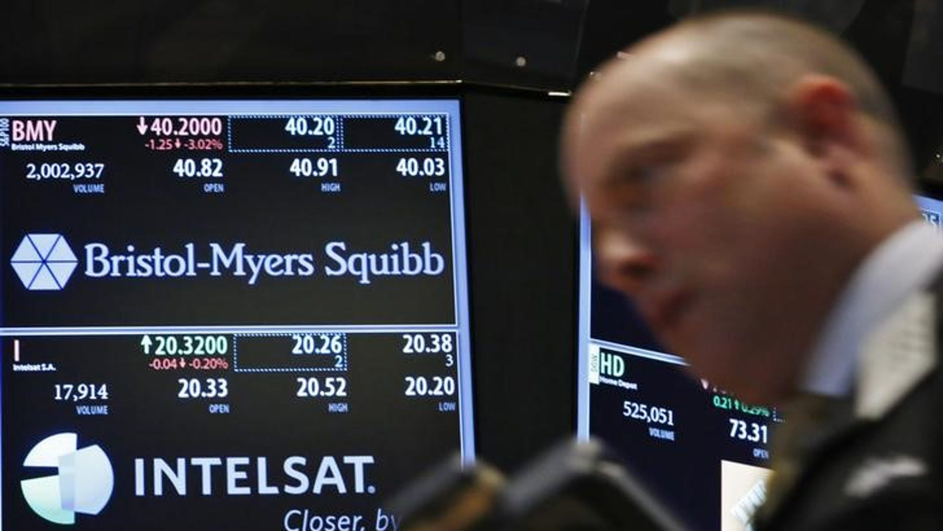 A trader passes by a screen displaying the tickers symbols for Bristol-Myers Squibb and Intelsat, Ltd. on the floor at the New York Stock Exchange