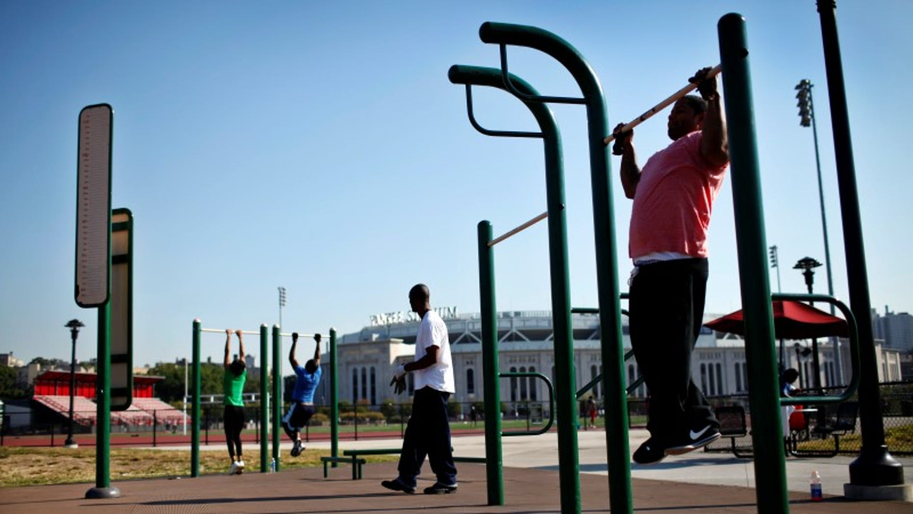 "People work out in an outdoor ""Adult Playground"" exercise area at Macombs Dam Park in the Bronx section of New York City"