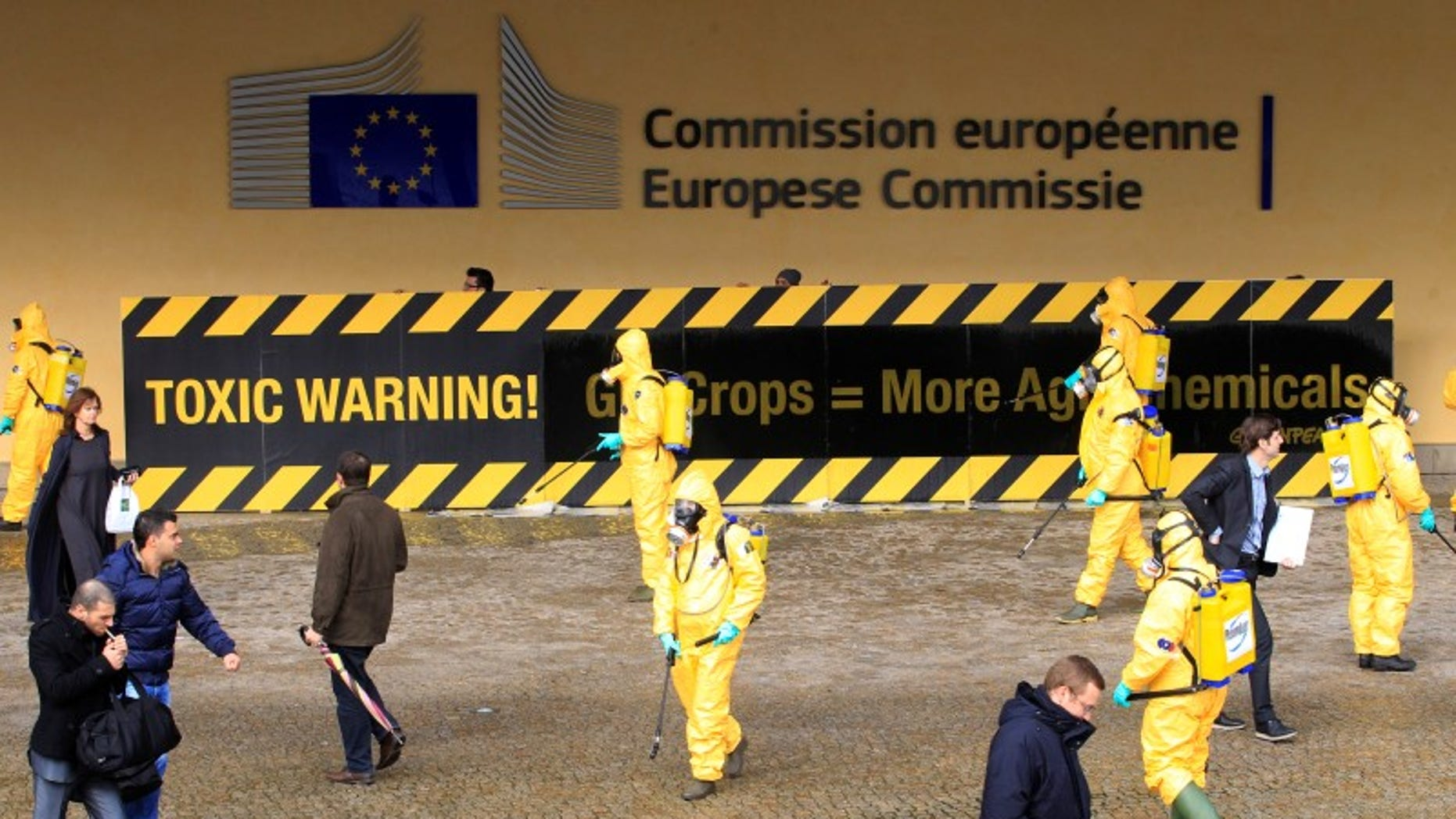 Activists of environmental group Greenpeace wear masks and protective clothing while protesting outside the European Commission headquarters in Brussels