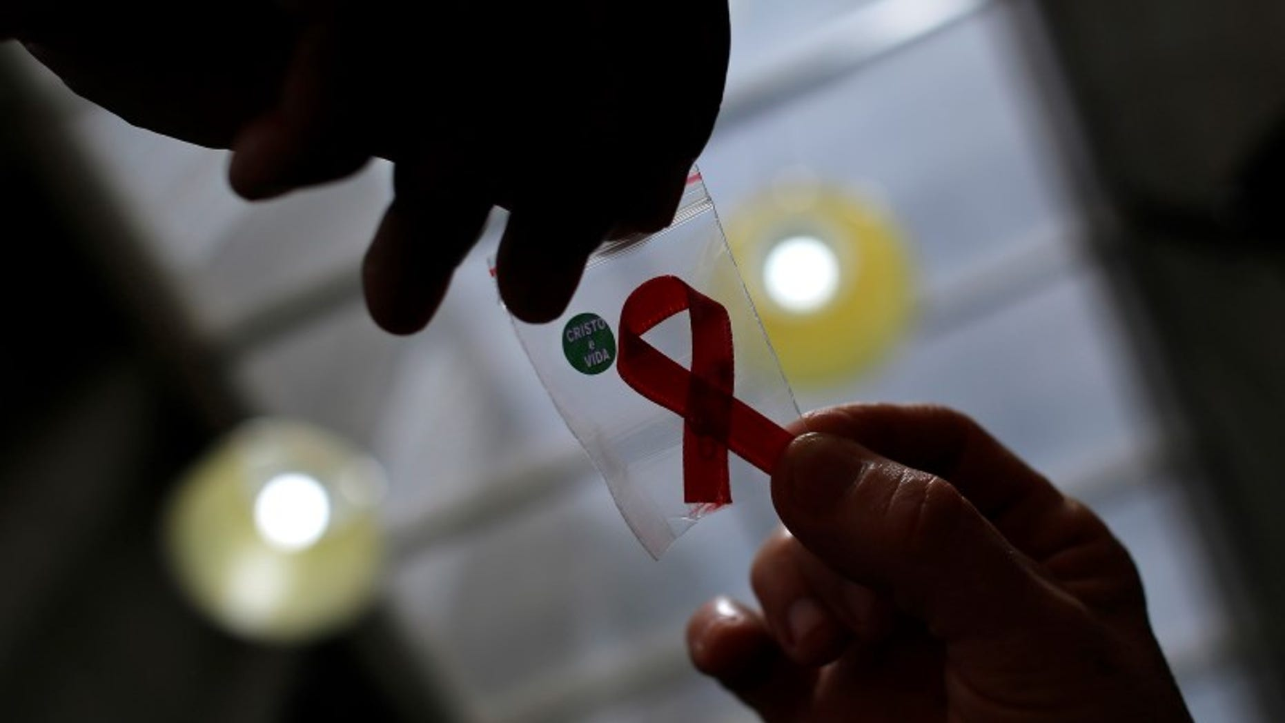 Nurse gives a red ribbon to a woman to mark World Aids Day at the entrance of Emilio Ribas Hospital, in Sao Paulo