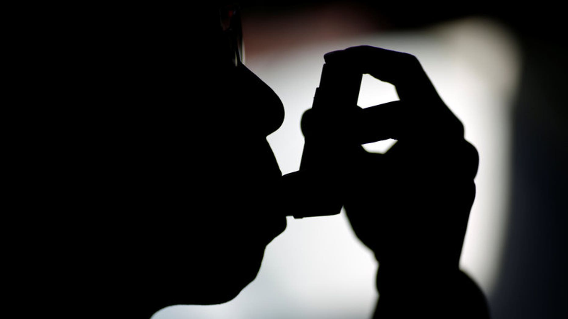 FILE PHOTO A man uses an inhaler at his house in Beijing, China