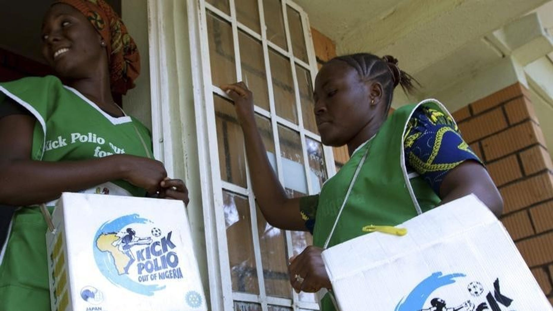 Volunteer Health officials wait to immunise children at a school in Nigeria's capital Abuja