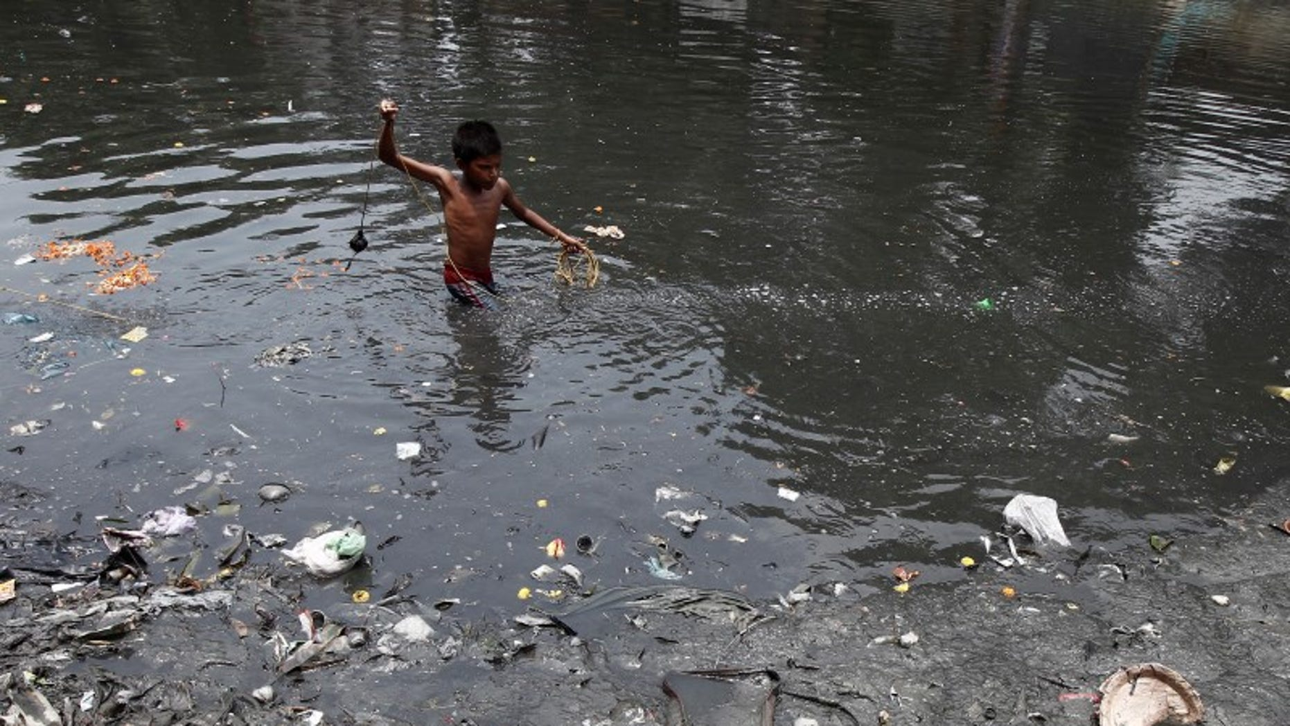 A boy searches for coins thrown by devotees as religious offerings in a polluted water channel near a temple in Kolkata