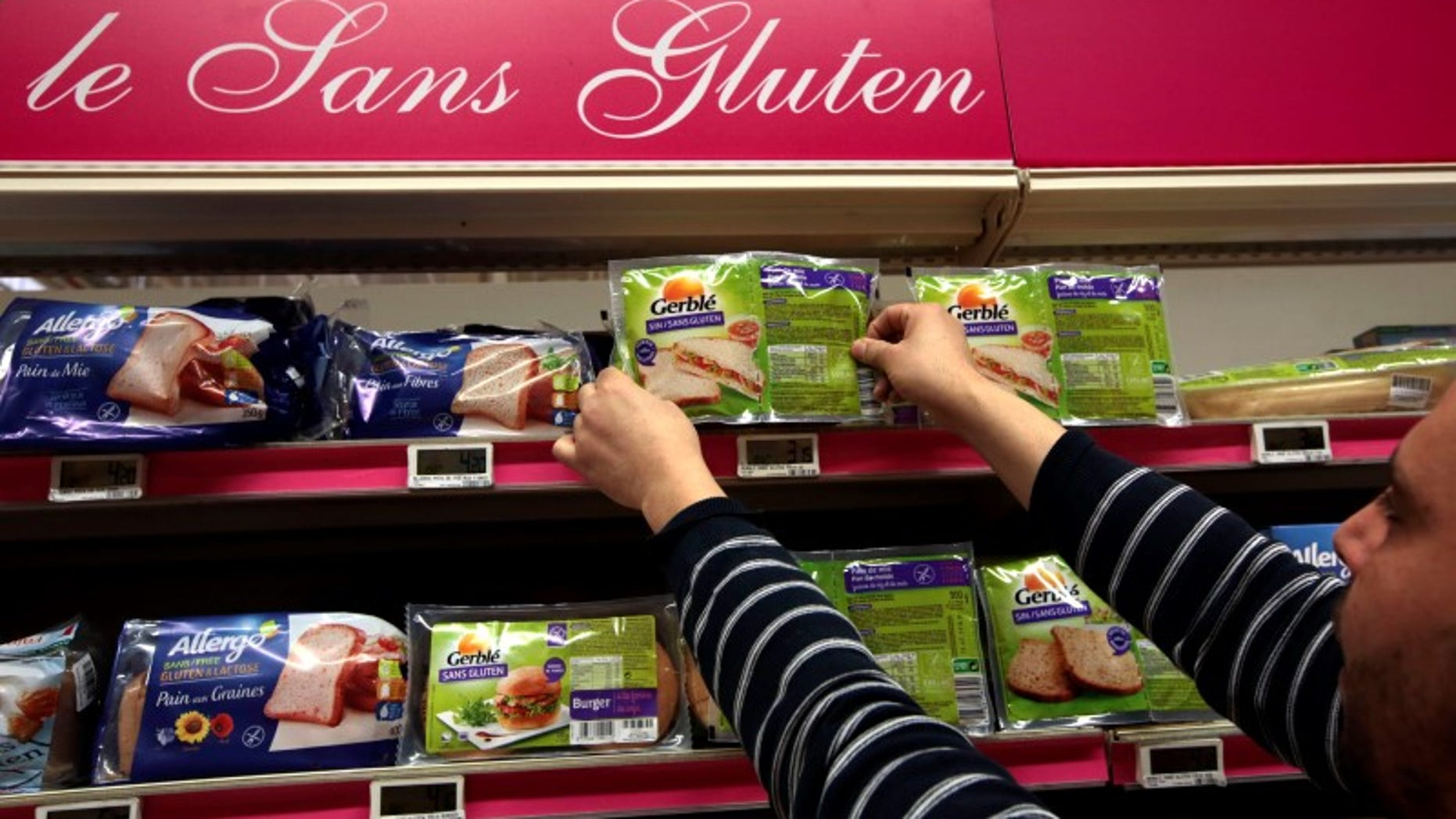 An employee arranges gluten-free products in a supermarket in Nice
