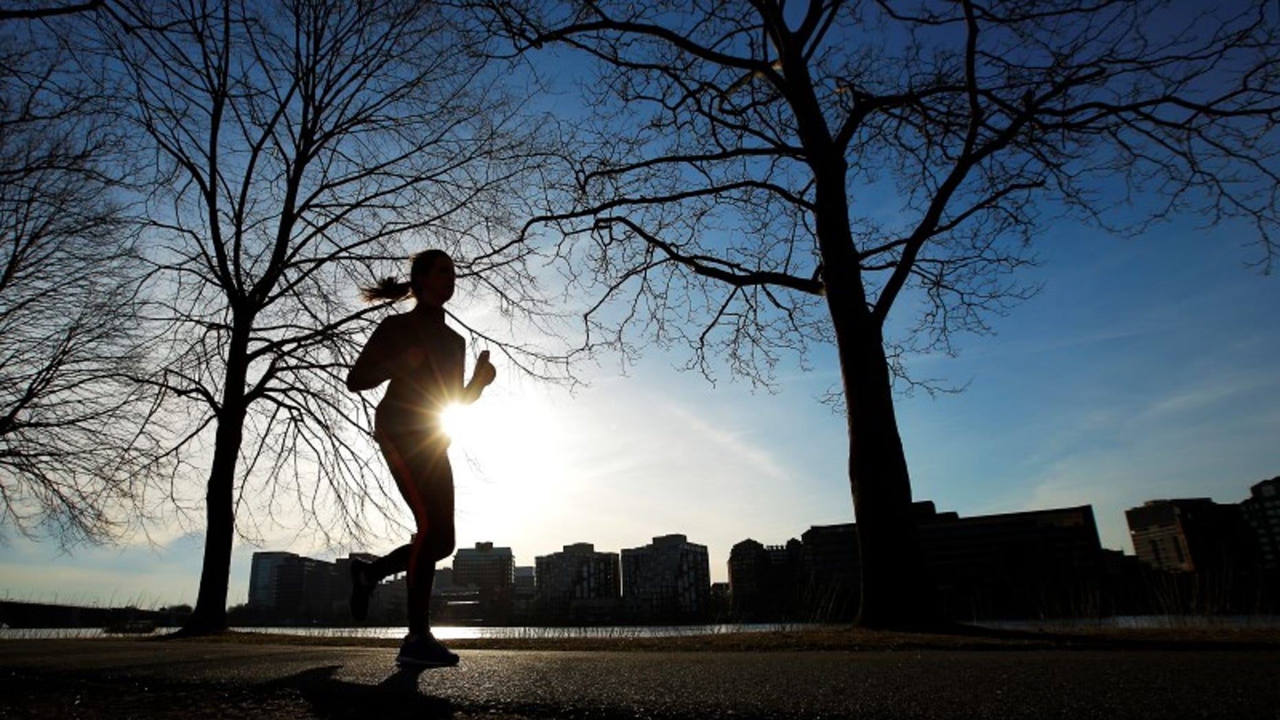 A woman jogs along the Charles River on an early spring evening in Boston.