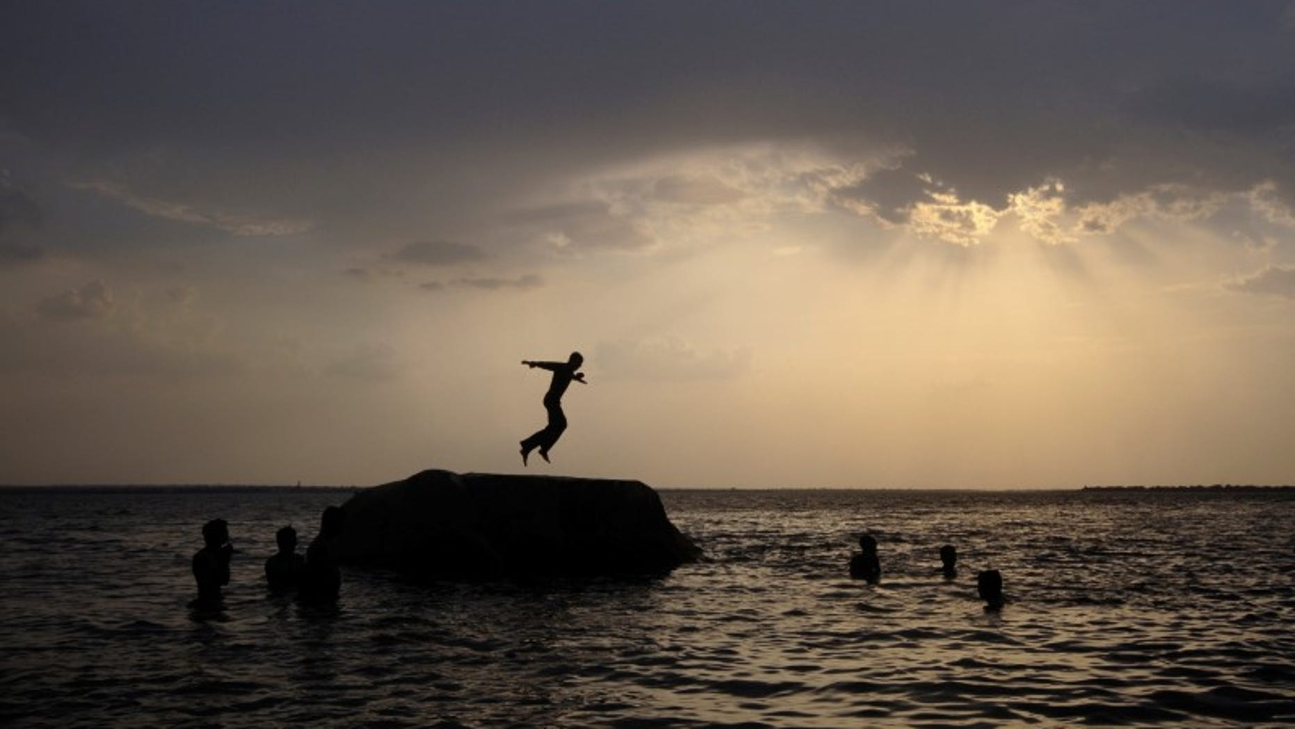 A boy prepares to jump off a rock into the waters of the Osman Sagar Lake near Hyderabad