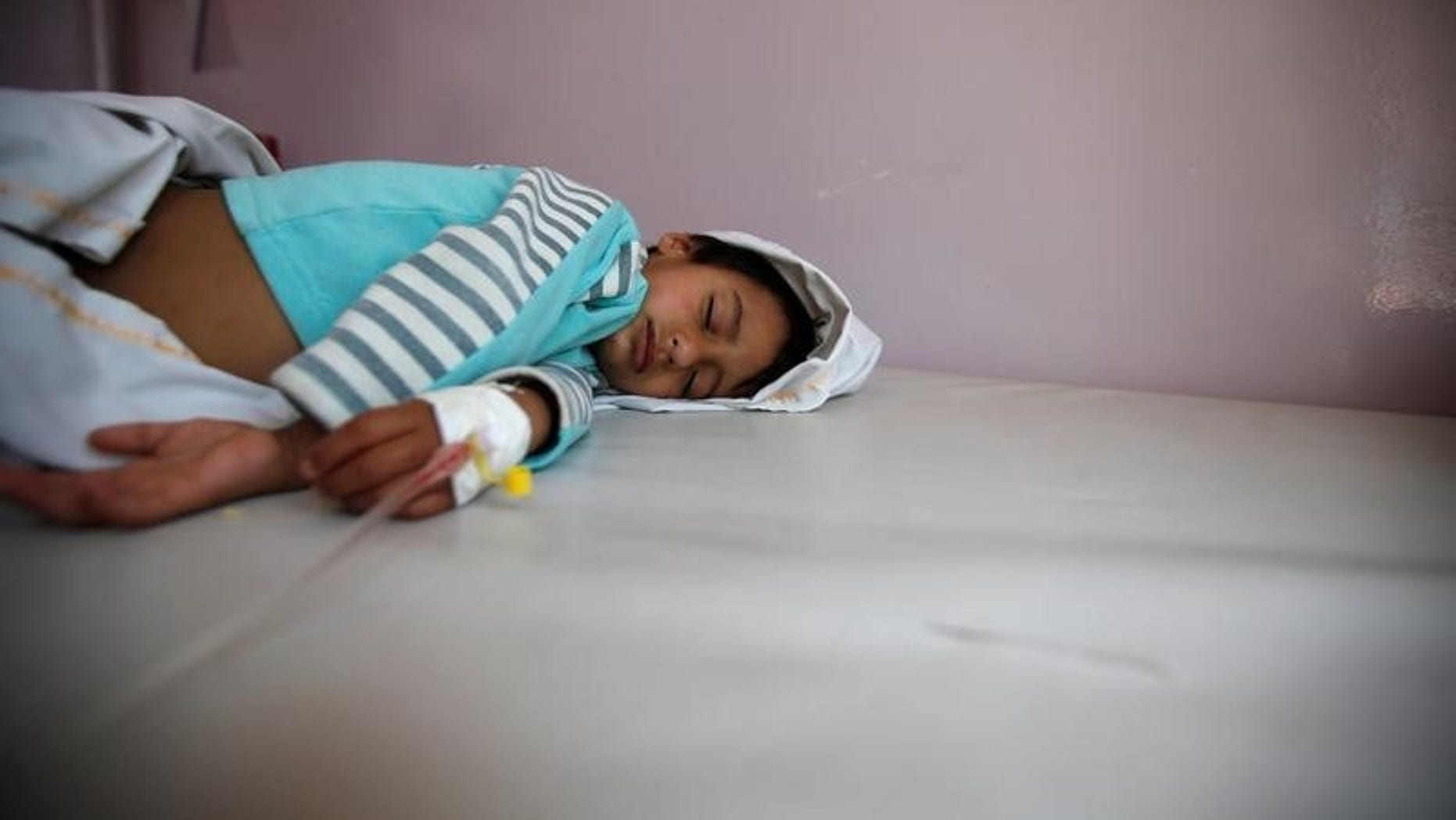 Boy lies on a bed at a hospital where he is receiving treatment for cholera amid confirmation by the UNICEF and the World Health Organization of an outbreak of the epidemic in Sanaa, the capital of Yemen