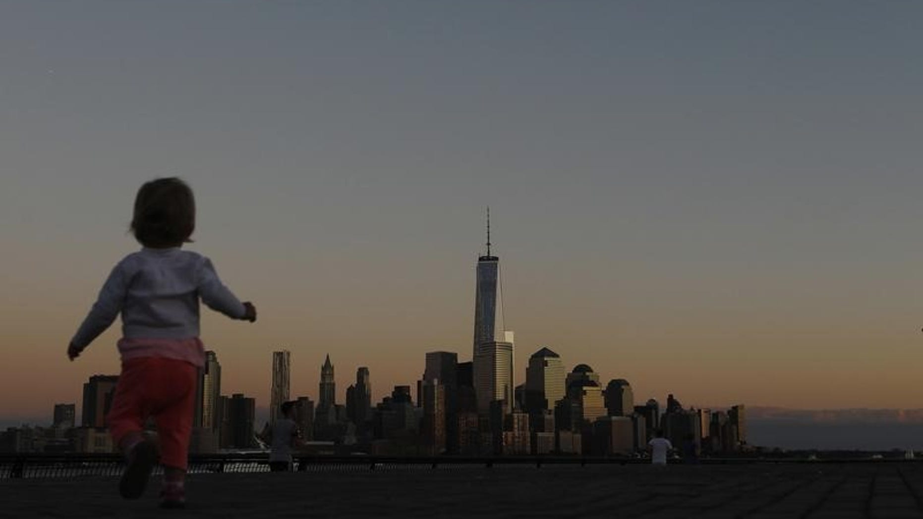 A girl plays in front of the skyline of New York's Lower Manhattan and One World Trade Center in a park along the Hudson River in Hoboken