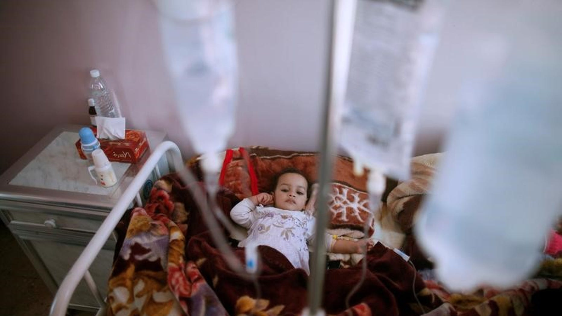 A girl lies on a bed at a cholera treatment center in Sanaa, Yemen