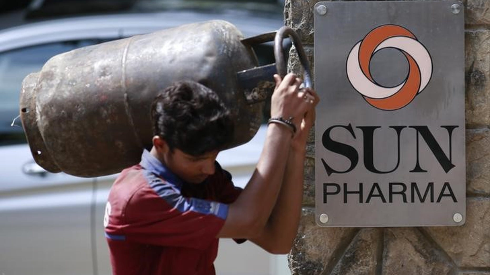 A man carrying gas cylinder walks out of research and development centre of Sun Pharmaceutical Industries Ltd in Mumbai