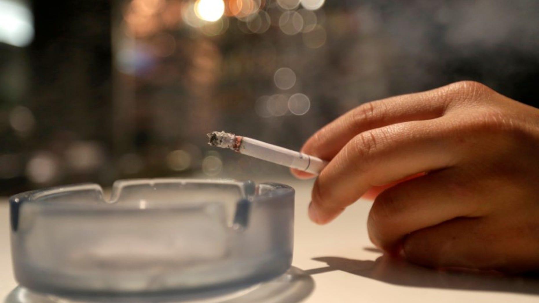A customer smokes a cigarette in a cafe in Prague