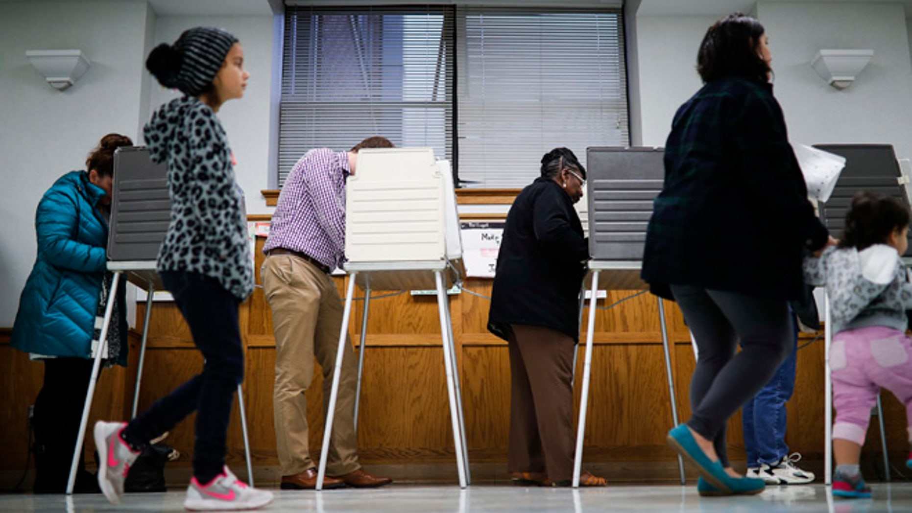 Voters fill out their ballots at the Nativity School polling place on Election Day, Tuesday, Nov. 8, 2016, in Cincinnati. (AP Photo/John Minchillo)