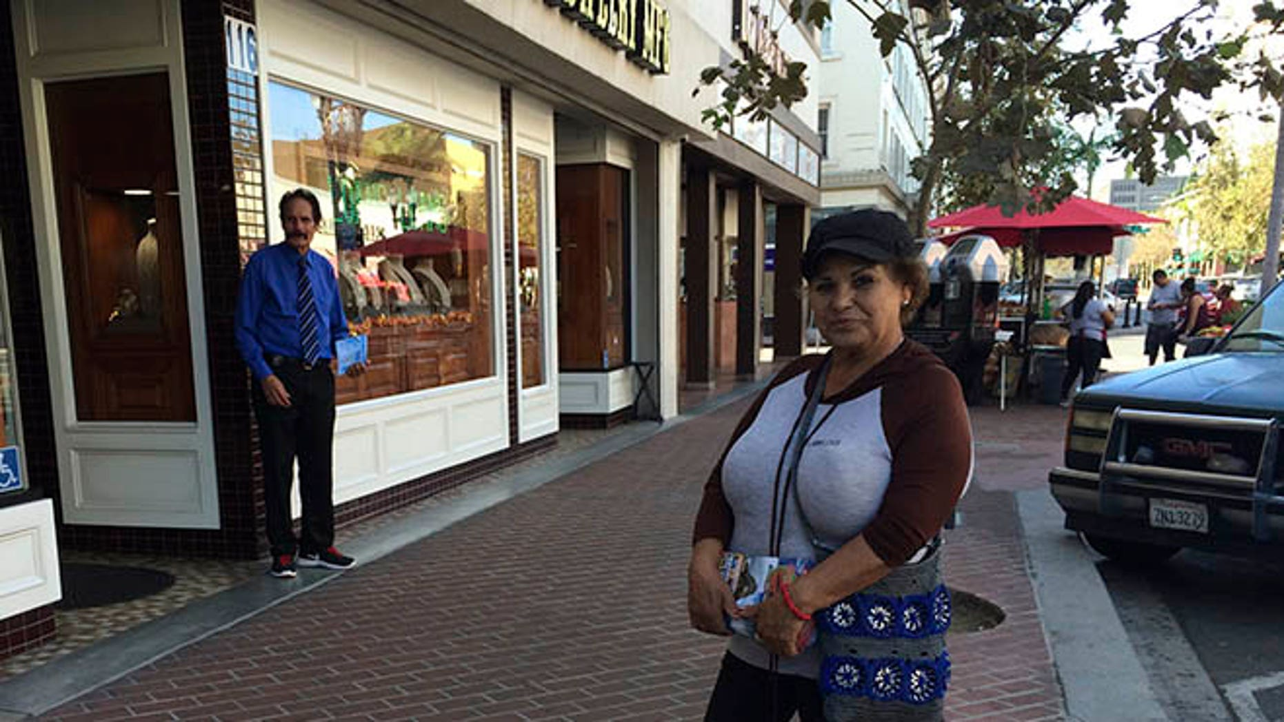 Alicia Ramirez, 67, hands out fliers to passers-by on a busy street in a largely Latino area lined with money transfer businesses and shops selling elegant gowns for quinceanera celebrations, on Wednesday, Nov. 9, 2016, in Santa Ana, Calif. She said she's afraid of what a Trump victory will mean for immigrants like her who lack legal papers. (AP Photo/Amy Taxin)