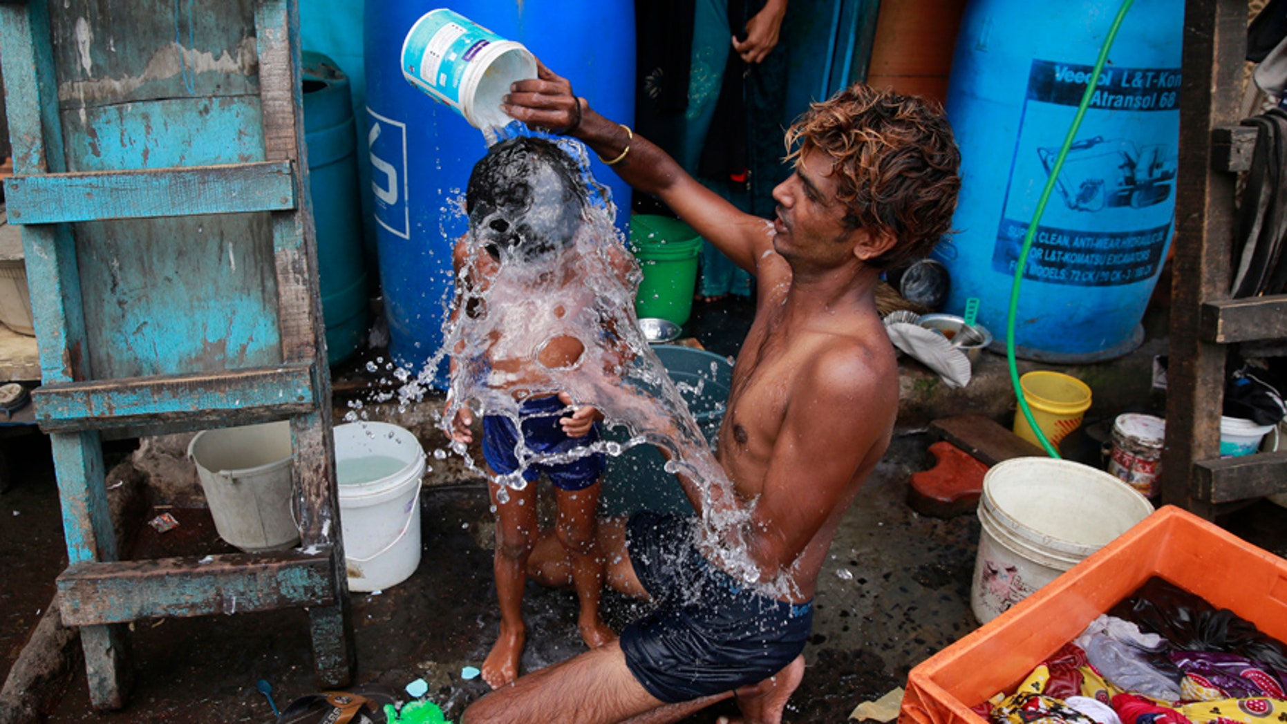 In this May 23, 2016, file photo, a man bath his son on a hot afternoon in a slum in Mumbai, India. For the third straight year, Earth set a record for the hottest year, NOAA and NASA announced.