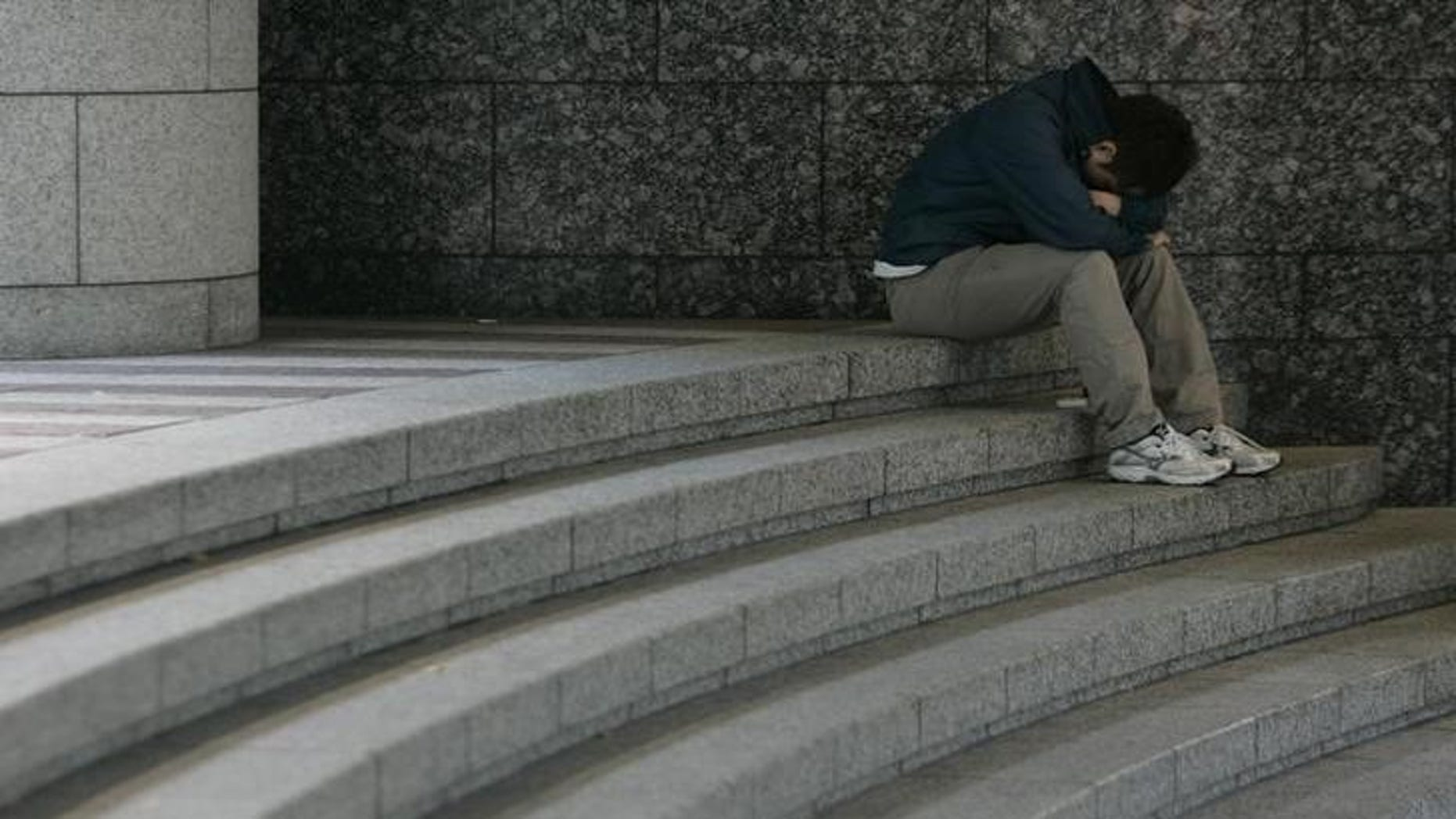 A man sits hunched over on a staircase in Tokyo