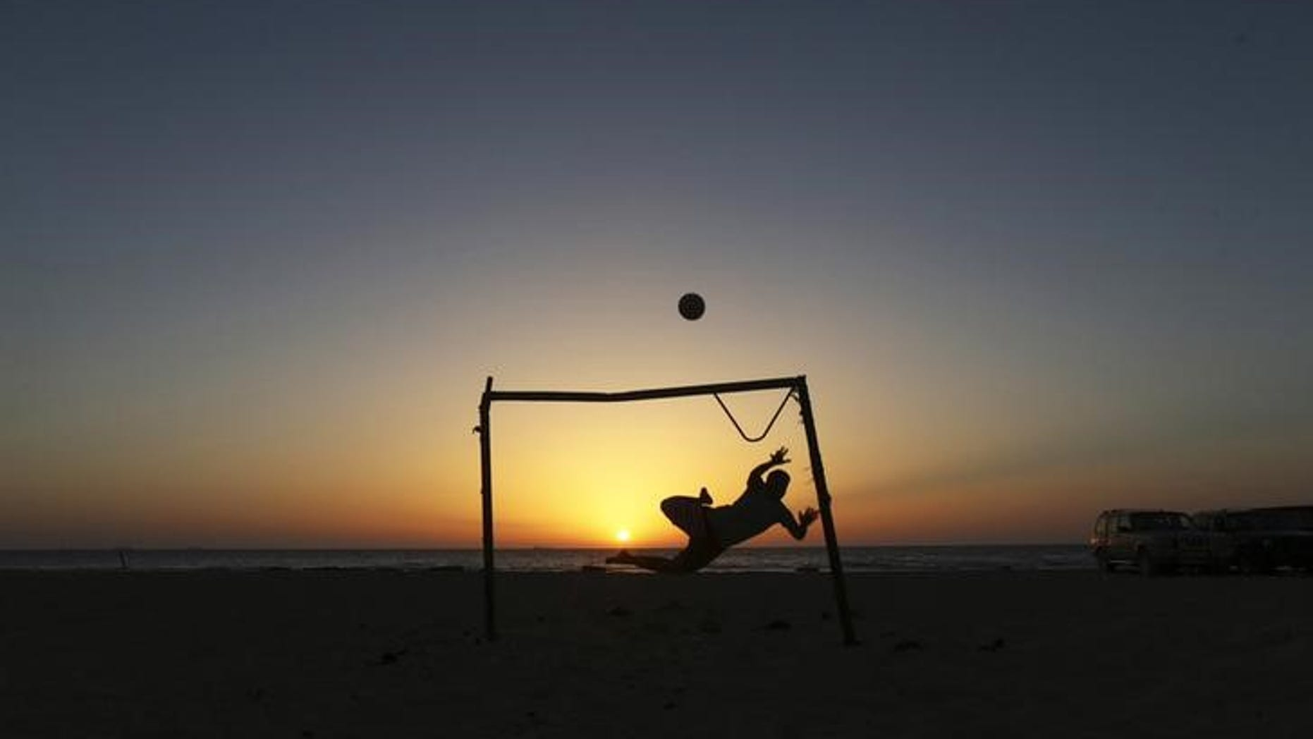 A boy jumps to save a goal while playing soccer on the beach in Benghazi