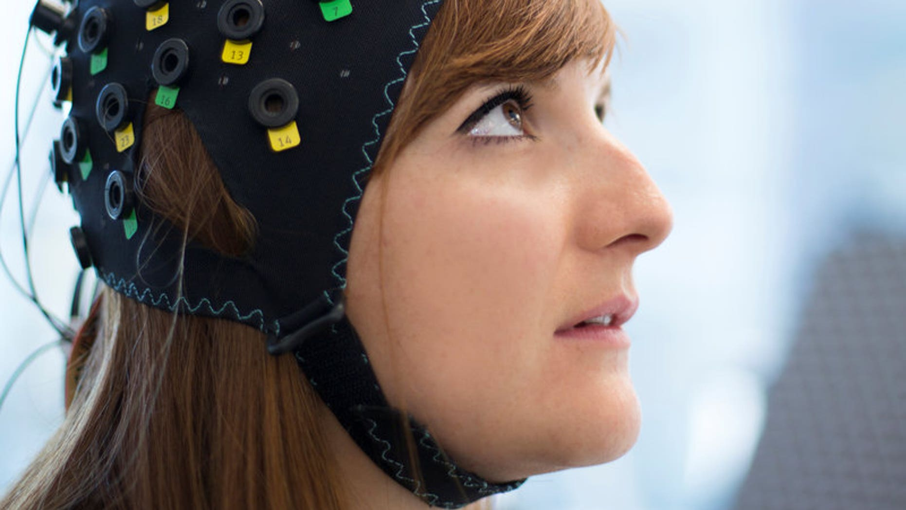 Handout photograph of the NIRS/EEG brain-computer interface system worn by a model