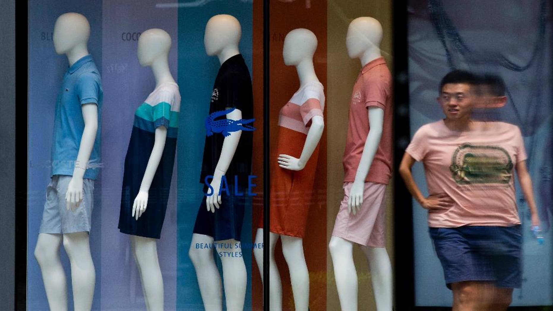 A man walks past mannequins with various fashion design clothes on display at a boutique in Beijing Tuesday, July 14, 2015. China's June export growth rebounded to 2.8 percent in a modest improvement amid slowing economic growth while imports fell 6.1 percent. (AP Photo/Andy Wong)