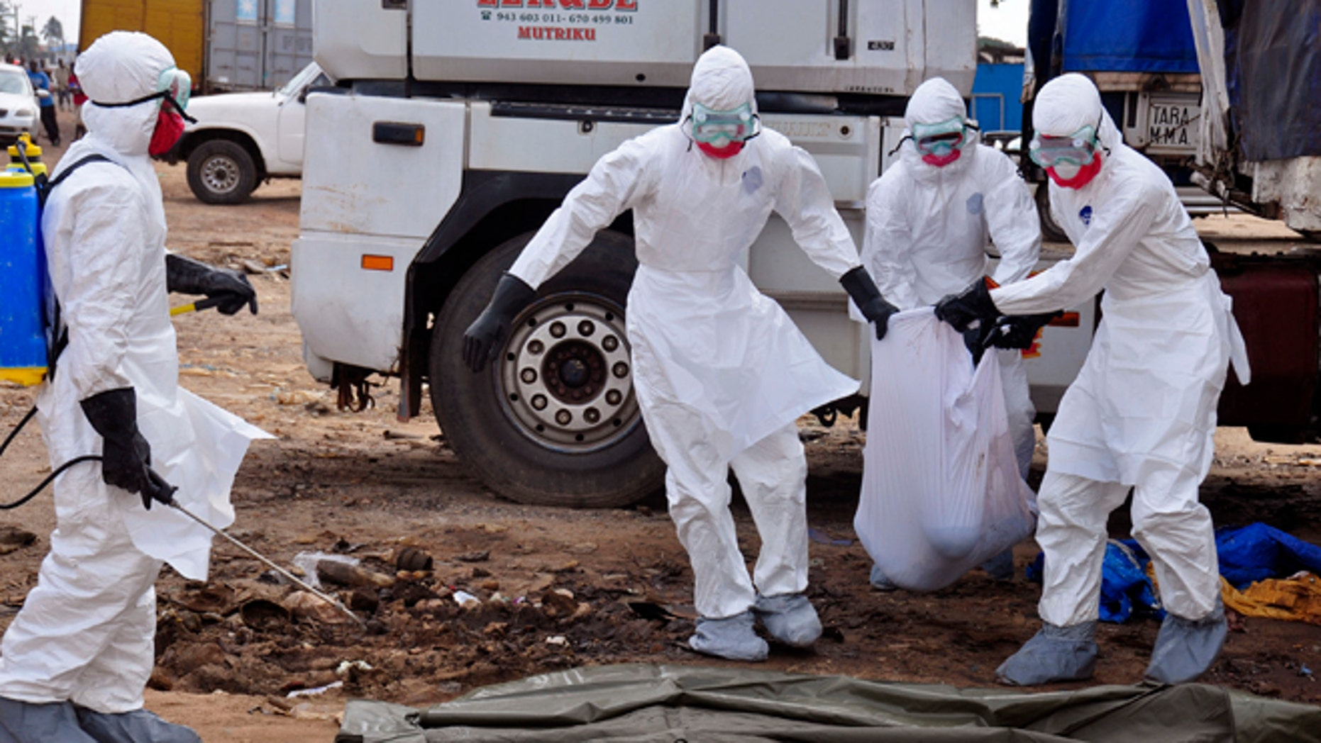 Health workers carry the body of a man found in the street, suspected of dying from the ebola virus,  in the capital city of Monrovia, Liberia, Tuesday, Aug. 12, 2014. The World Health Organization declared its ethical to use untested drugs and vaccines in the ongoing Ebola outbreak in West Africa although the tiny supply of one experimental drug handed out to three people has been depleted and it could be many months until more is available. (AP Photo/Abbas Dulleh)