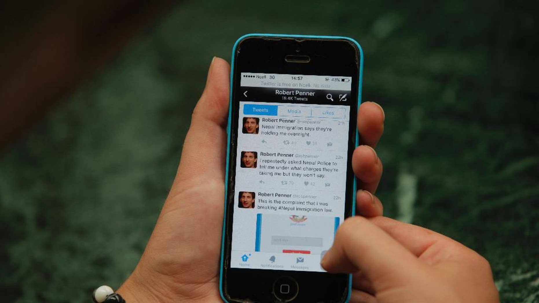Twitter page of Canadian man, Robert Penner is seen on the screen of a mobile phone in Kathmandu, Nepal, Tuesday, May 3, 2016. Nepalese officials say they have ordered Penner to leave the country within two days for posting messages on social media that could disturb social harmony. (AP Photo/Niranjan Shrestha)