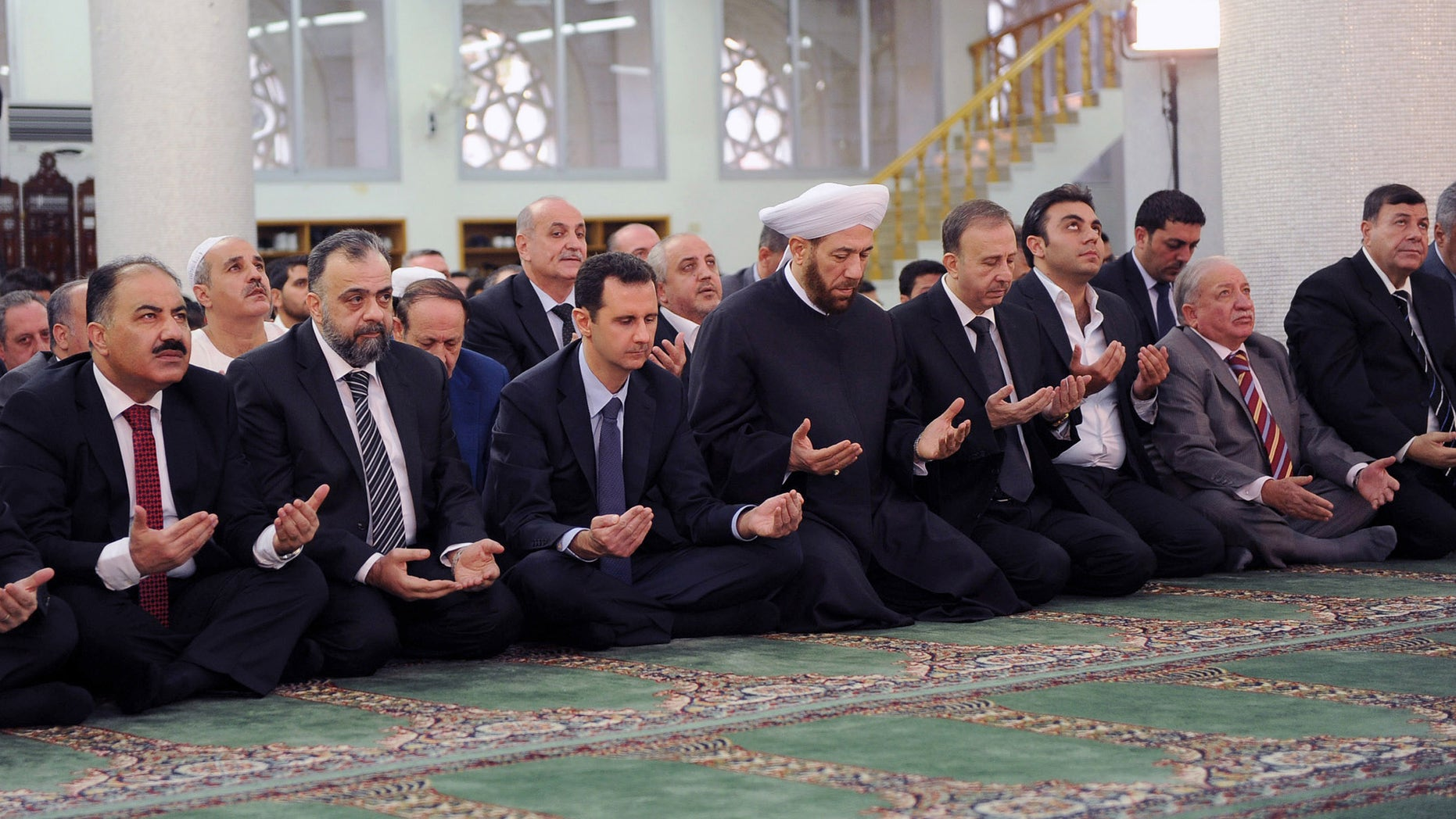 In this photo released by the Syrian official news agency SANA, Syrian President Bashar Assad, third left, prays on the first day of Eid al-Adha at the Sayeda Hassiba mosque, in Damascus, Syria, Tuesday, Oct. 15, 2013. (AP Photo/SANA)