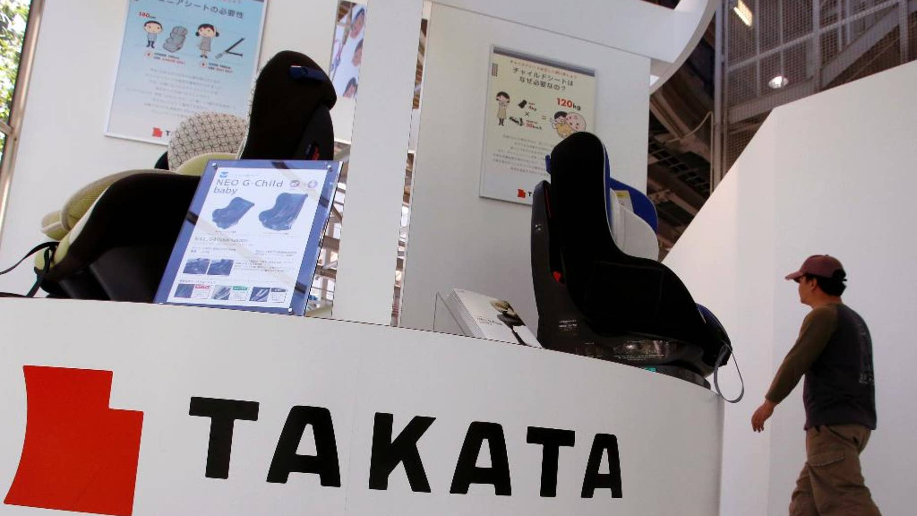 FILE - In this Wednesday, May 4, 2016 file photo, a visitor walks past child seats, manufactured by Takata Corp., displayed at an automaker's showroom in Tokyo.  A criminal complaint has been filed in Japan about a Takata air bag causing injuries during a crash, the first such case in this nation related to an unfolding massive recall. Takata Corp. said Wednesday, June 8, 2016,  it was fully cooperating with the investigation of the accident, in which a woman in the front passenger seat of a Nissan X-Trail sport-utility vehicle was injured.(AP Photo/Shizuo Kambayashi, File)