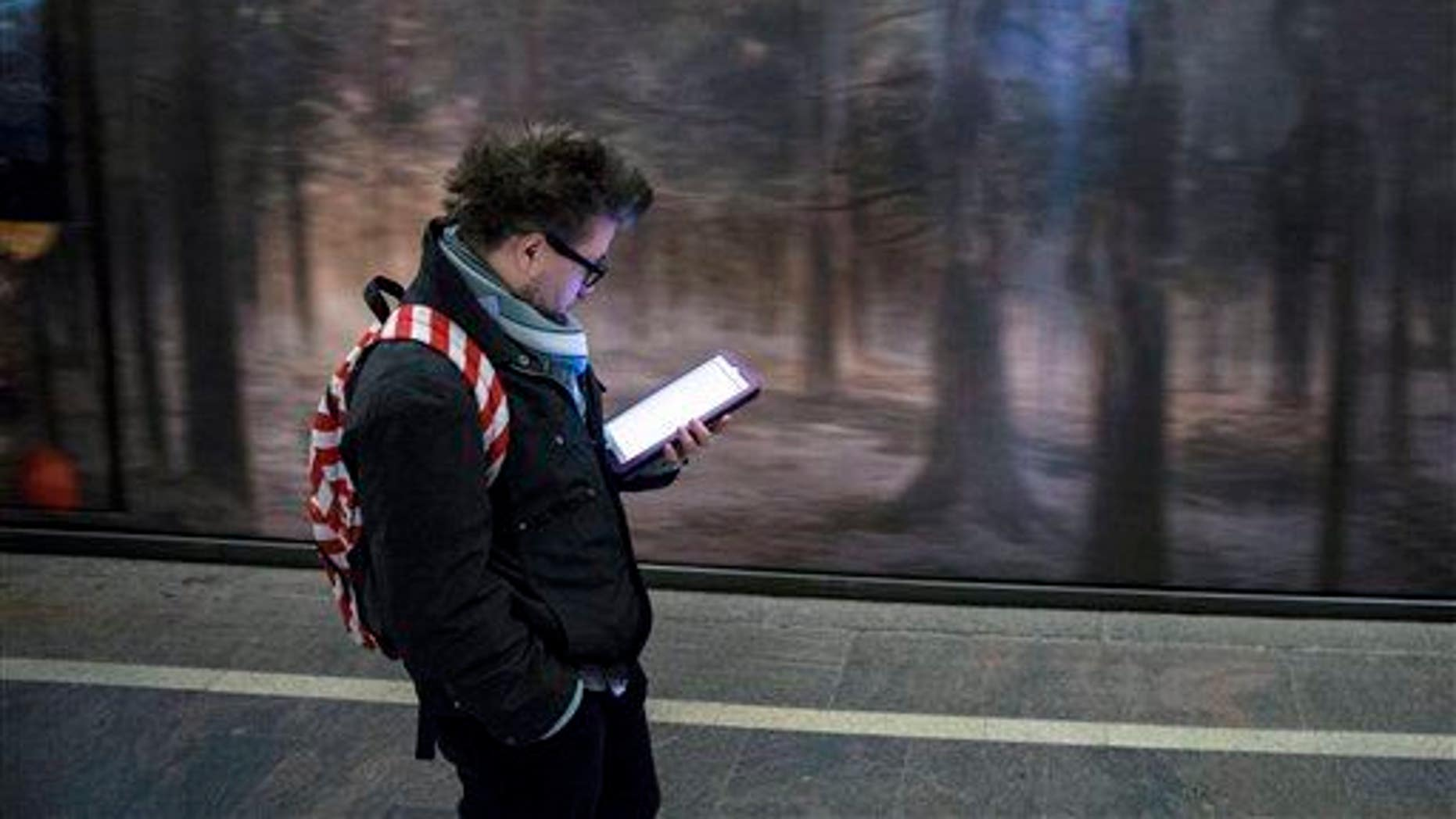 A man surfs the Internet on his tablet in a Moscow subway, Russia, Wednesday, April 8, 2015.